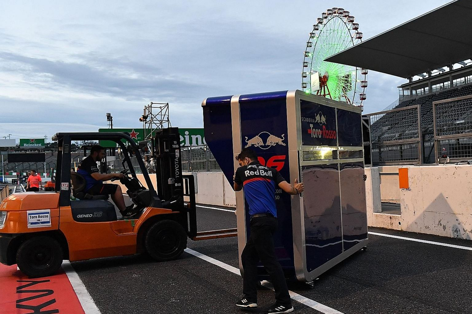 Toro Rosso mechanics removing the pit wall control desk soon after the two practice sessions for the Japanese Grand Prix at Suzuka circuit yesterday in preparation for Typhoon Hagibis' approach.