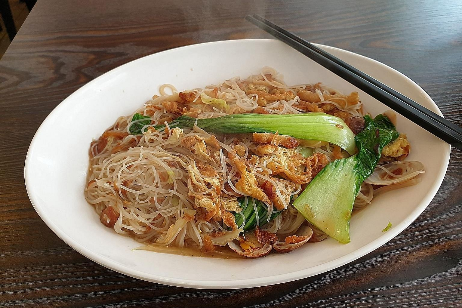 The vermicelli was bathed in a rich gravy and came with clams, fish cake, bok choy, finely sliced tau pok and wispy fried egg.