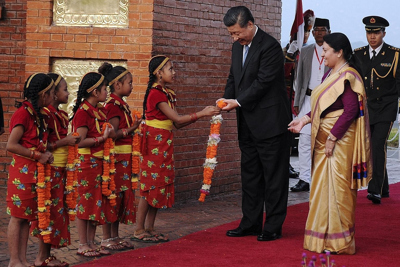 Chinese President Xi Jinping receiving garlands as he was accompanied by Nepal's President Bidya Devi Bhandari during a welcome ceremony at Tribhuvan International Airport in Kathmandu on Saturday. Mr Xi, the first Chinese President to visit in more