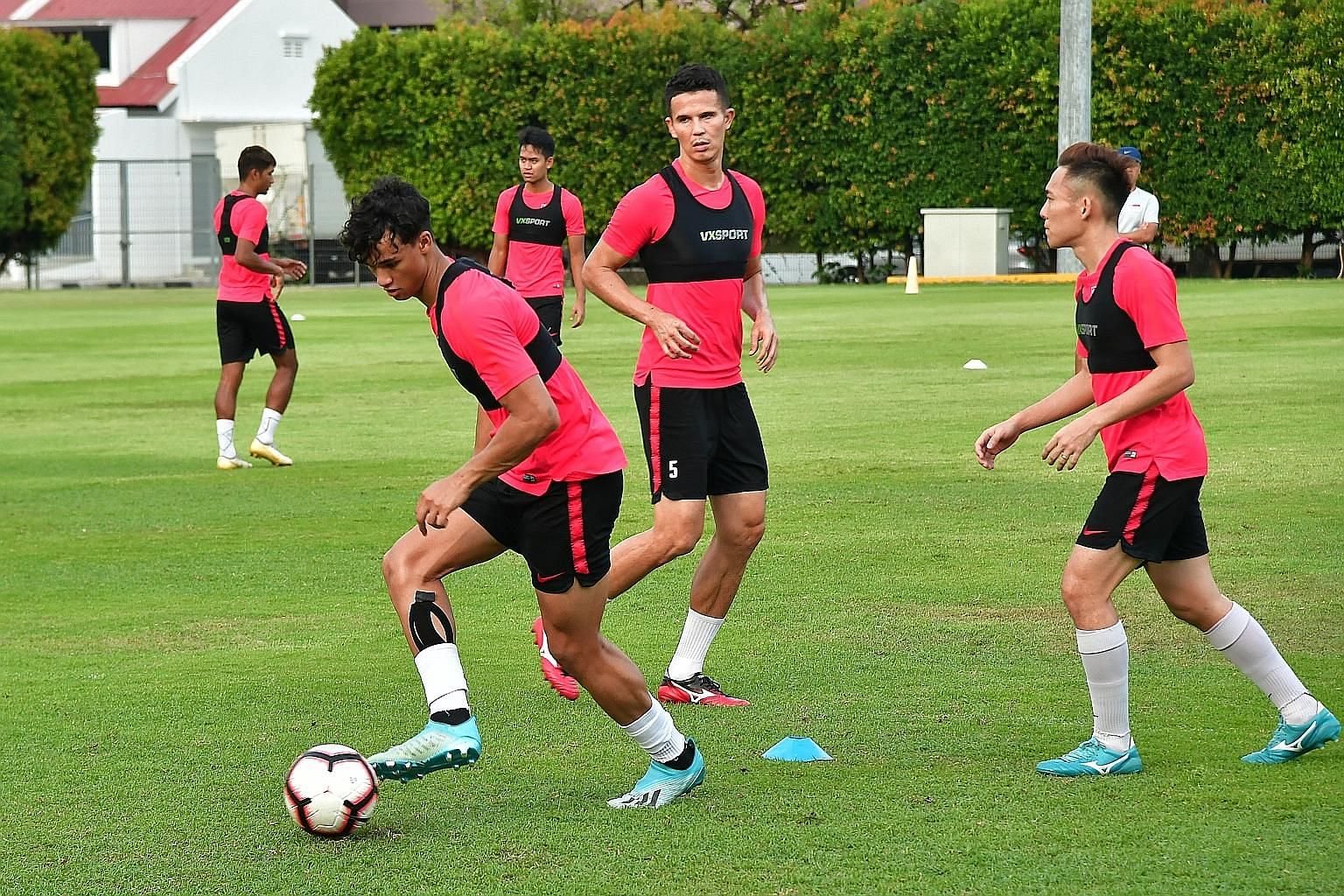 Ikhsan Fandi, watched by Baihakki Khaizan and Darren Teh, on the ball during Singapore's training session ahead of their game against Uzbekistan. ST PHOTO: DESMOND WEE