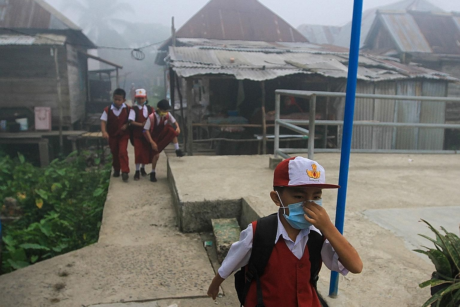 Schoolchildren donning face masks as thick haze caused by forest fires still burning across Indonesia blanketed Palembang yesterday, sending visibility plummeting to as low as 50m, and forcing most schools around the city to close. The Air Pollutant