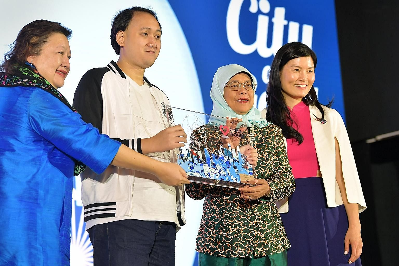 Mr Faris Wong, an artisan from social enterprise Personalised Love, presenting a token of appreciation that he worked on with two others to President Halimah Yacob at the launch of the National Volunteer and Philanthropy Centre's new vision yesterday