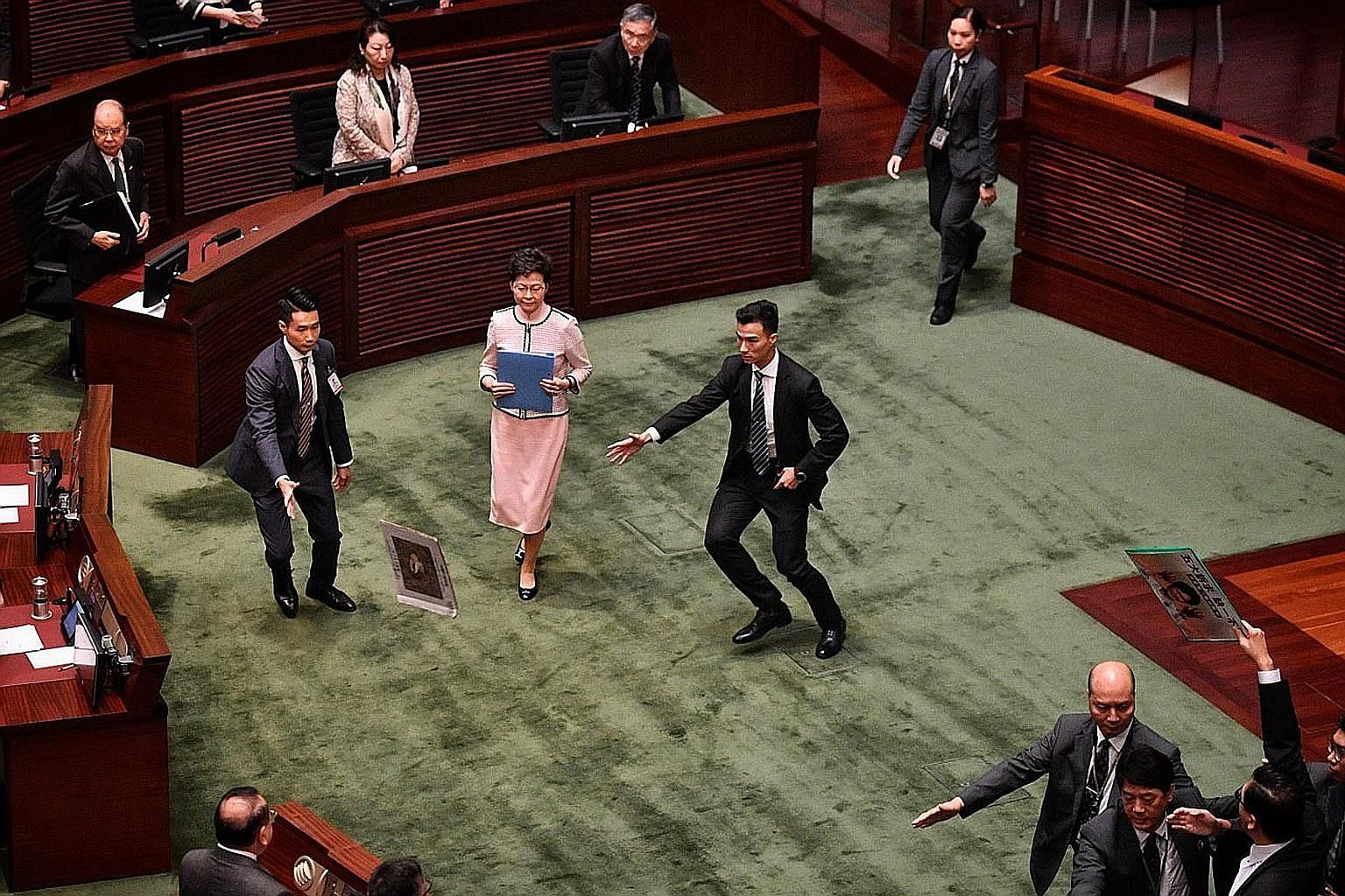 Security aides rushing to shield Hong Kong Chief Executive Carrie Lam after a pro-democracy legislator threw a placard at her while she was leaving the Legislative Council yesterday. Pro-democracy lawmakers disrupted Mrs Lam's annual policy address,
