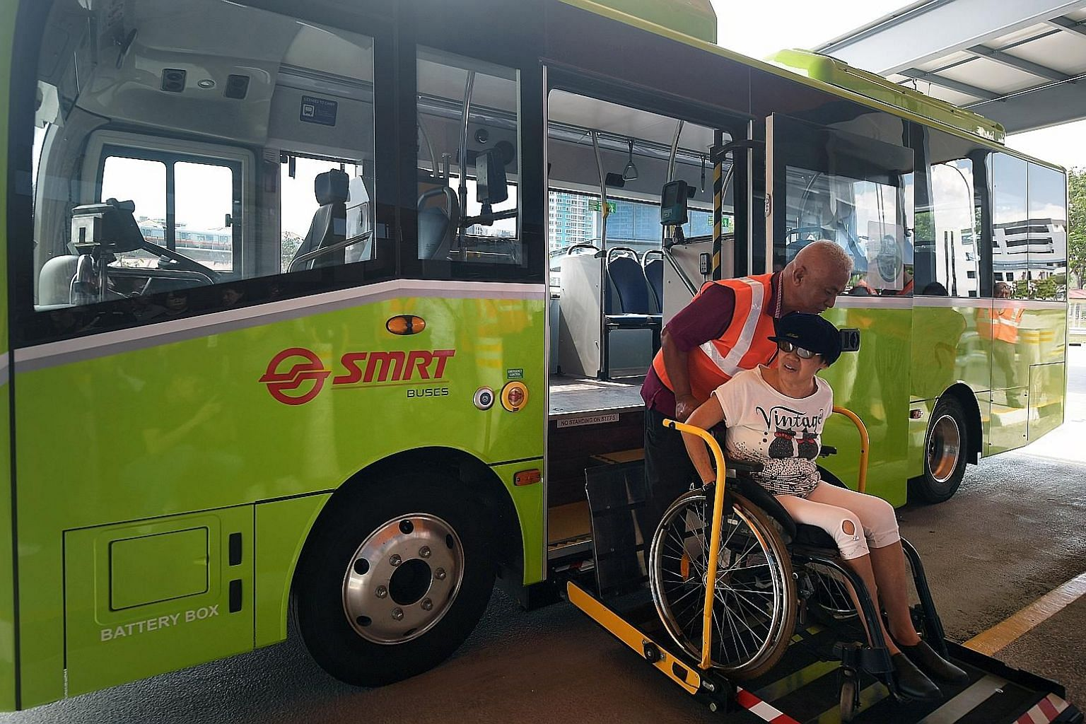 Left: The expanded Yio Chu Kang bus interchange boasts green features, wheelchair-friendly boarding points and more bicycle parking spaces. Above: Ms Wendy Tan boarding service 825's new electric minibus with the help of bus captain Ramli Khamis yest