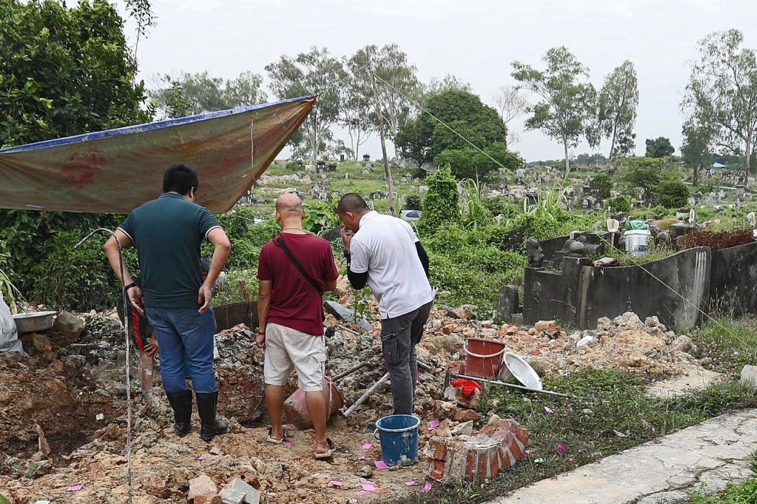 National Environment Agency workers conducting exhumations at Choa Chu Kang Chinese Cemetery. The agency said this is the first time it has encountered this misalignment issue in the 16,800 exhumations conducted as of Sept 30 under Phase 7 of its exh