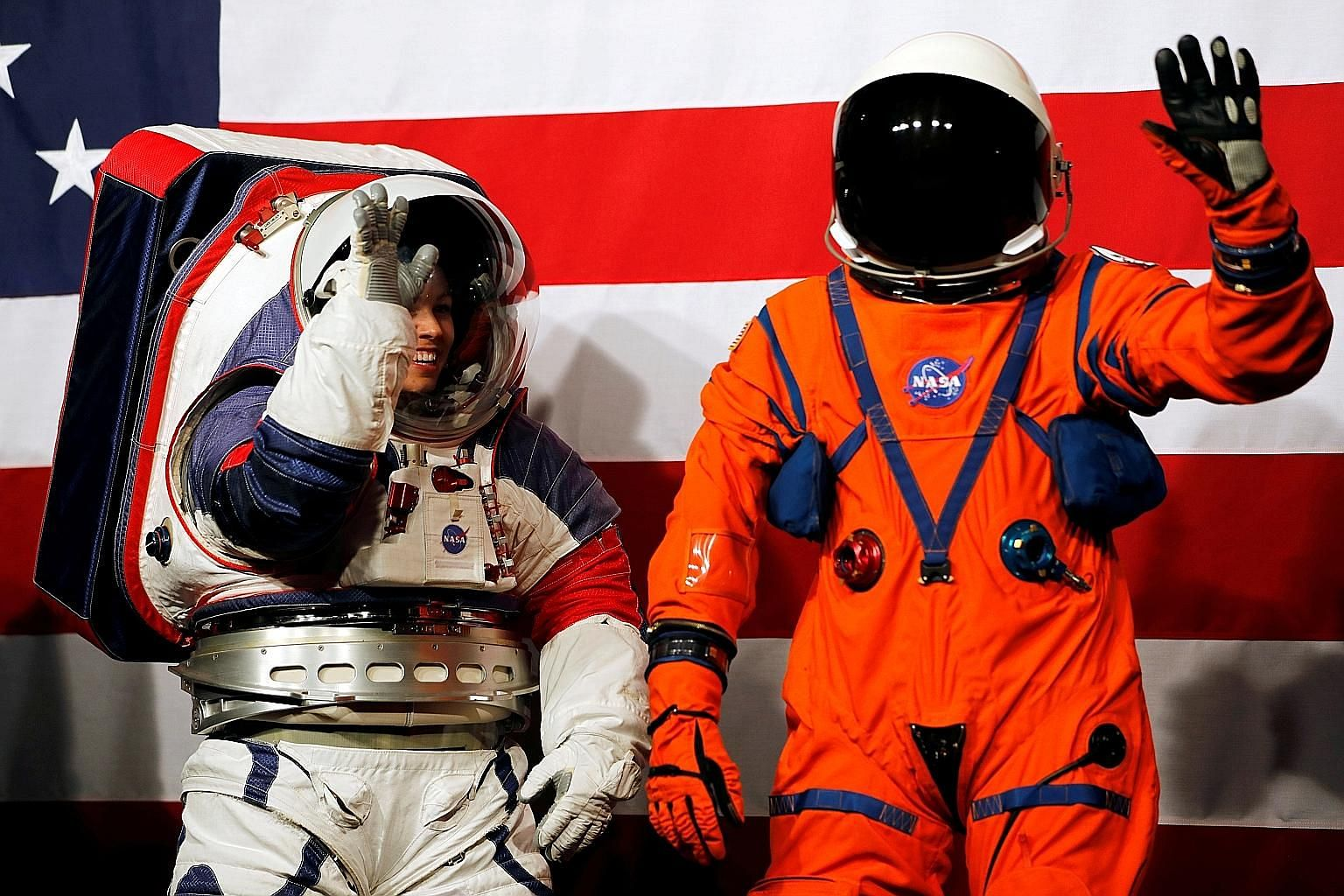 The white xEMU spacesuit and the orange Orion Crew Survival spacesuit being presented at Nasa headquarters in Washington on Tuesday.