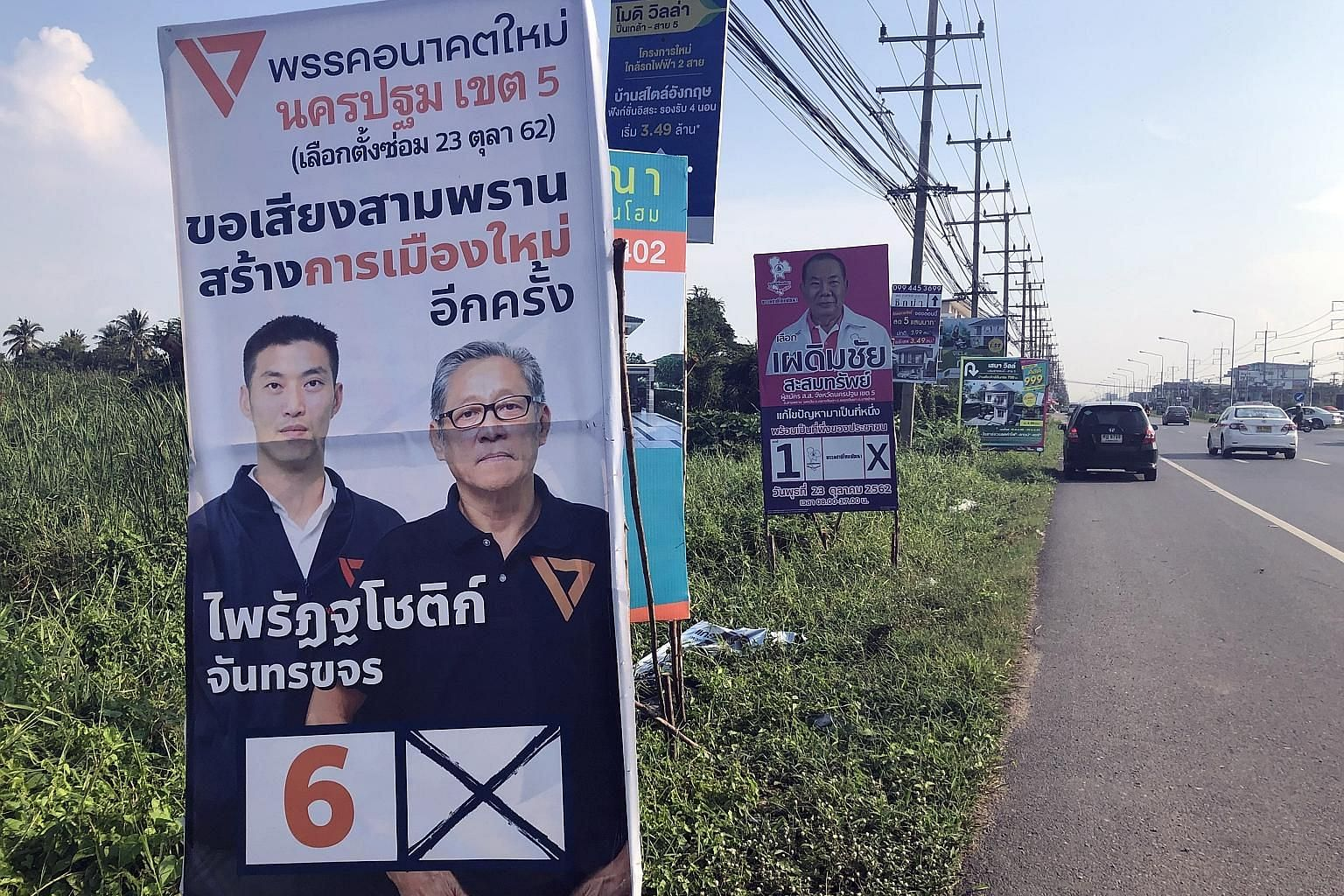 Campaign posters for the Future Forward Party (left) and Chart Thai Pattana Party in Nakhon Pathom province. Future Forward's Chumpita Juntarakajorn, who won in March, resigned for health reasons.