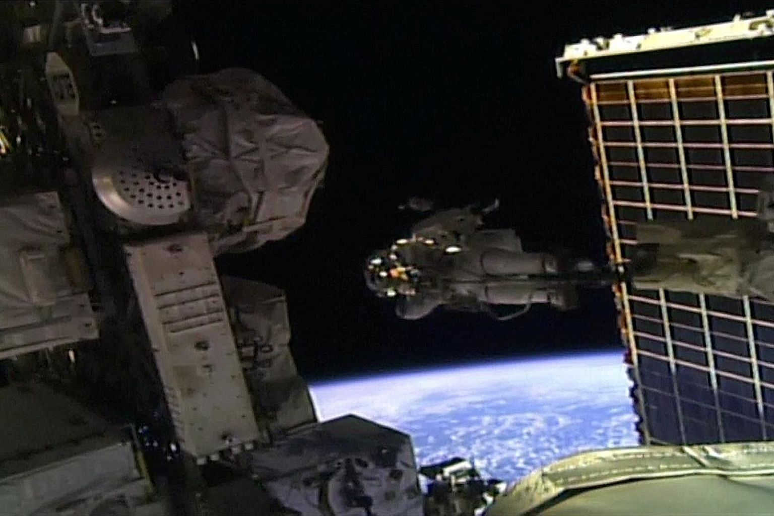 A still image (left) from a Nasa video showing Ms Jessica Meir (above) walking outside the International Space Station yesterday. With her on the spacewalk was Ms Christina Koch (top).