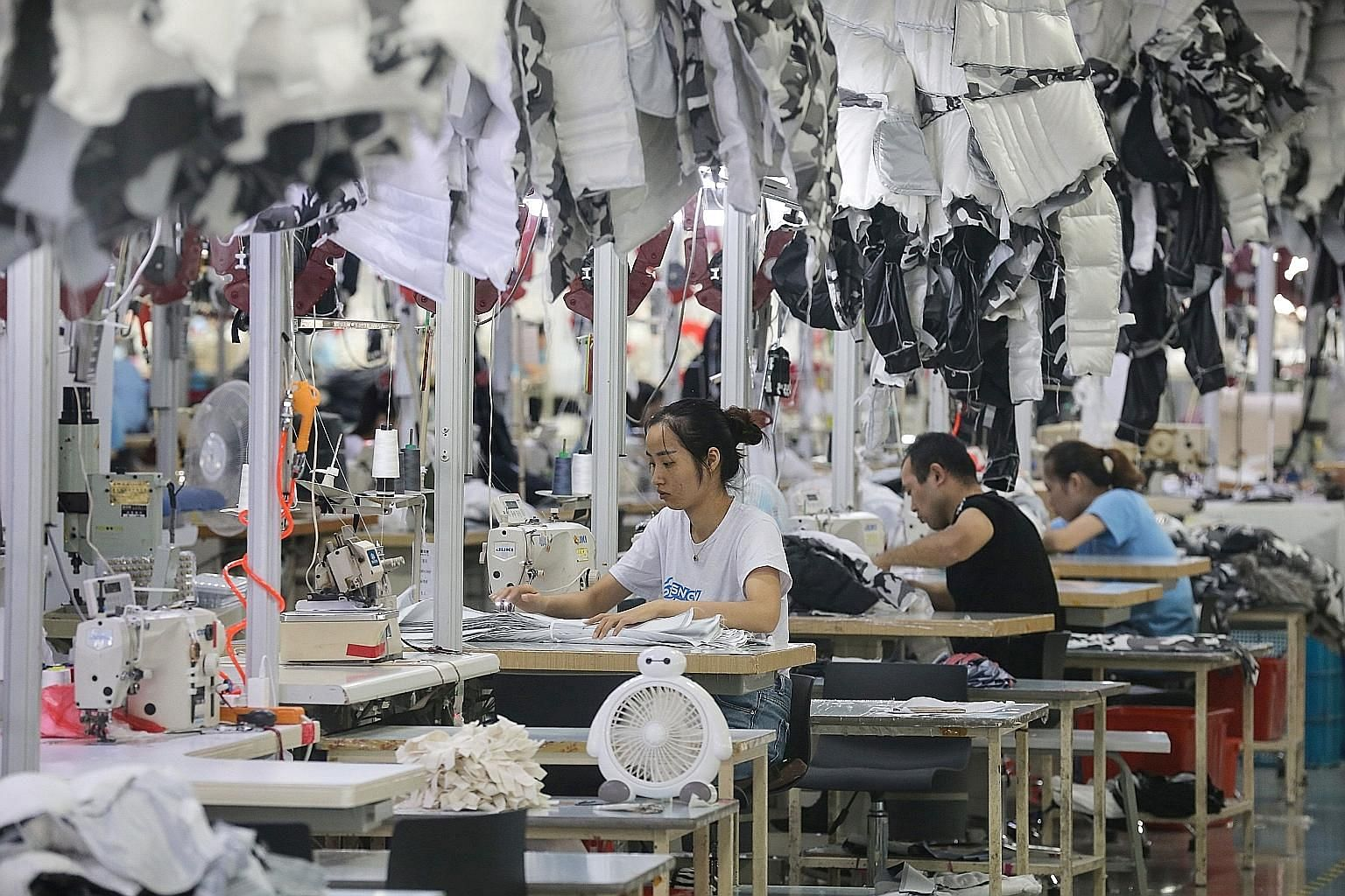 Employees producing down coats at a clothing factory in Nantong, China. China's economic growth has been hit by soft factory production amid a bruising Sino-US trade war. PHOTO: AGENCE FRANCE-PRESSE