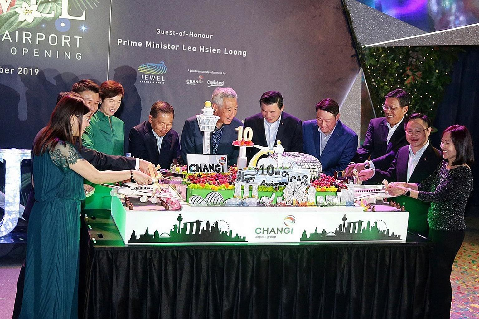 Prime Minister Lee Hsien Loong cutting a cake yesterday to celebrate Changi Airport Group's 10th anniversary with (from left) CAG's executive vice-president of commercial Lim Peck Hoon; CAG's executive vice-president of airport management Tan Lye Tec