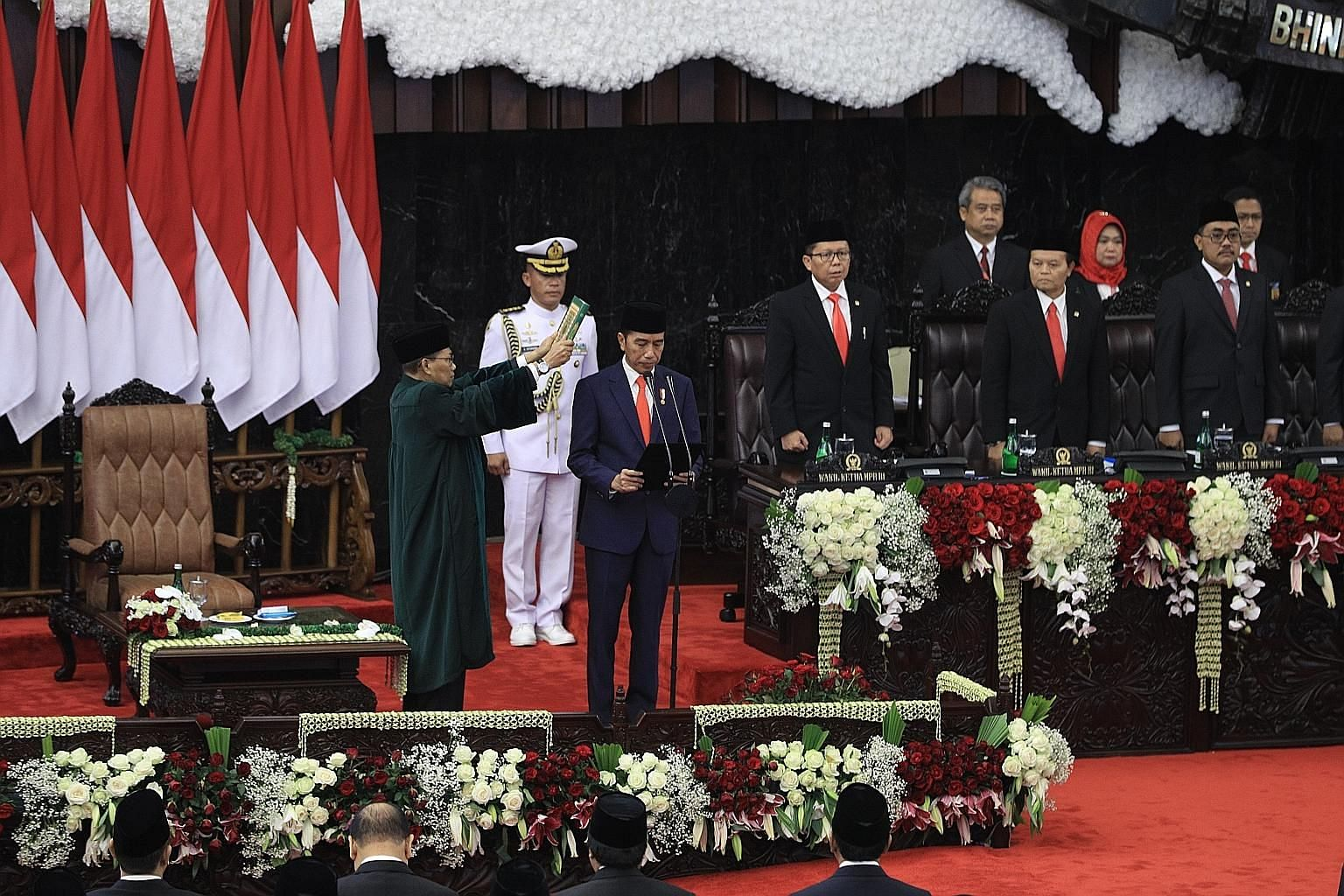 Indonesian President Joko Widodo reciting the oath of office, with a Quran held over his head, at the Parliament building in Jakarta yesterday. In his speech later, he urged Indonesians to stay nimble in the face of challenges.