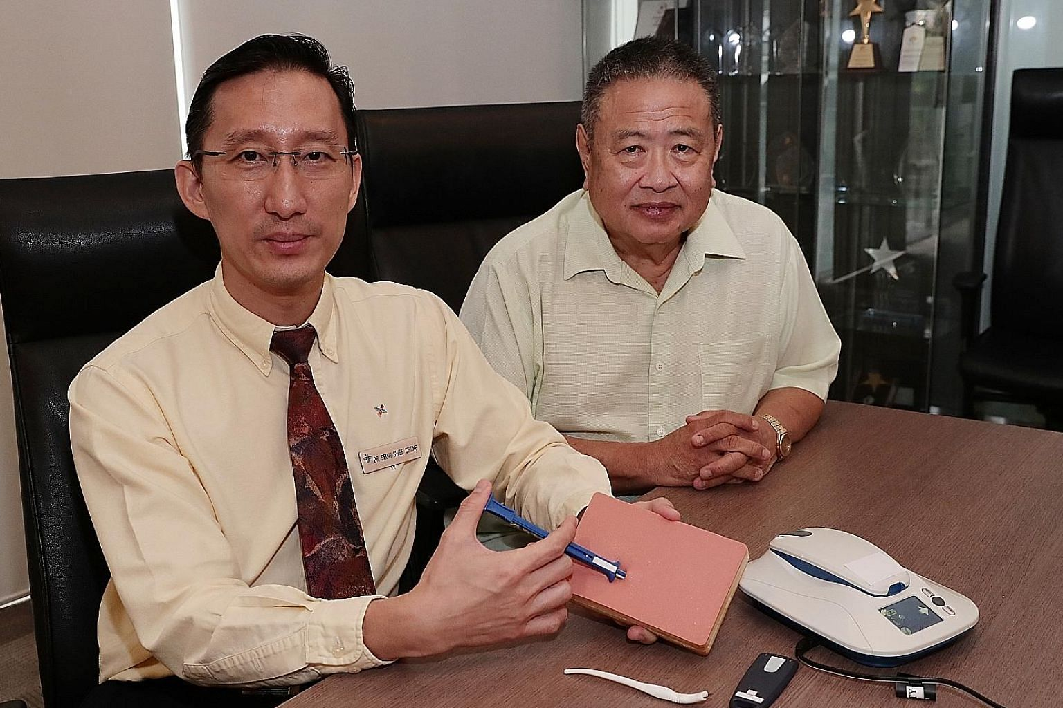Dr Seow Swee Chong (left), a senior consultant at the National University Heart Centre's Department of Cardiology, and his patient Ng Kok Seng, 65, who has an Insertable Cardiac Monitor implanted in his chest. In the picture, Dr Seow is demonstrating