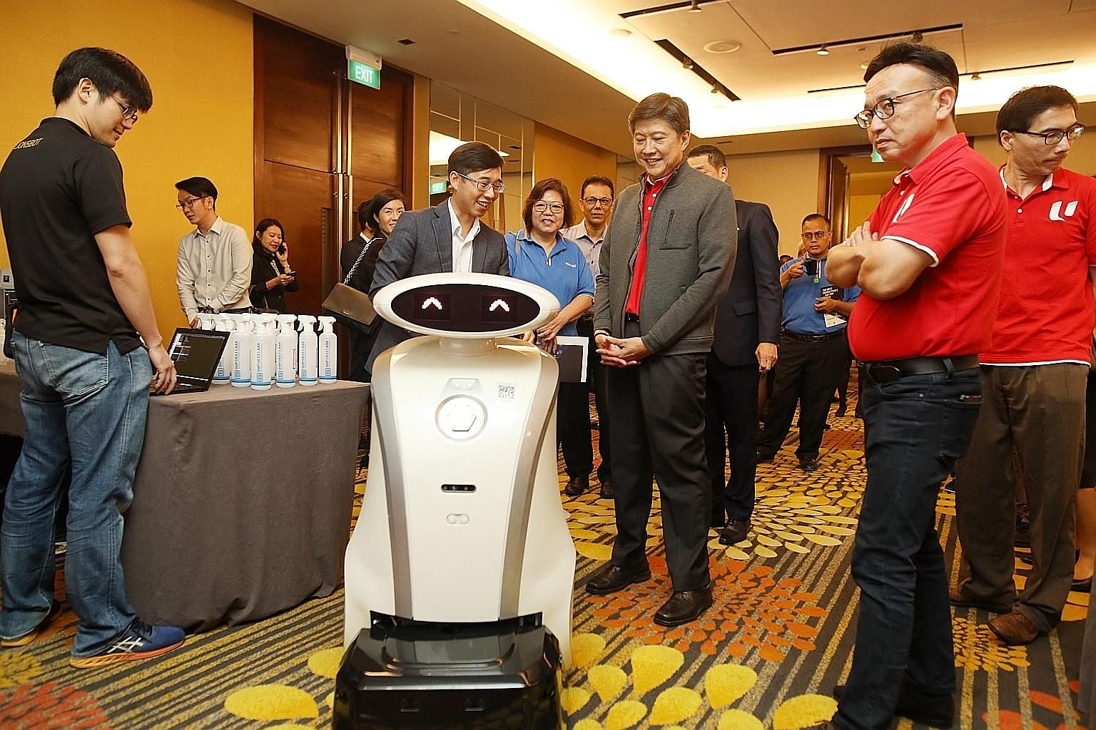 NTUC secretary-general Ng Chee Meng (centre) observing Ella, a robot that vacuums carpeted areas and greets guests in hotel environments, at the Copthorne King's Hotel yesterday.