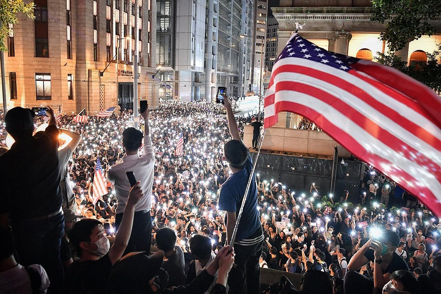 Protesters in Hong Kong flying the American flag near government headquarters last week. The territory's neoliberal tendencies and hands-off developmental approach has seen the world pass it by while persistent social problems remain unaddressed, say