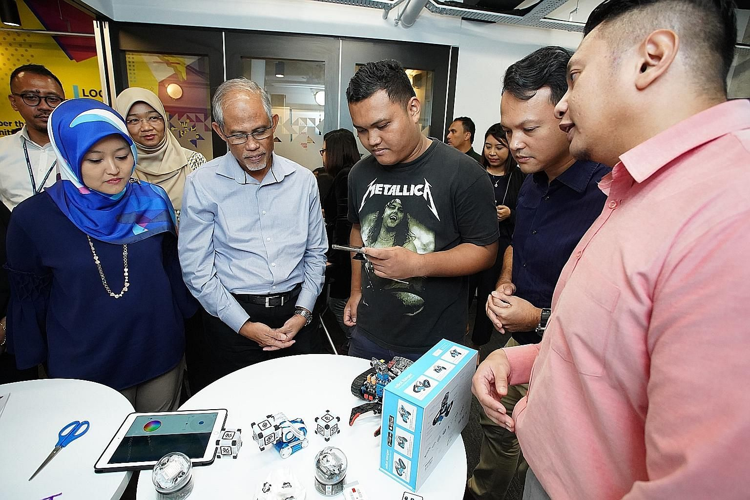 Minister-in-charge of Muslim Affairs and Mendaki chairman Masagos Zulkifli at a robotics booth at the launch of the satellite centre in Jurong yesterday. With him are (from left) MP for Jurong GRC Rahayu Mahzam, ITE College West student Zulkarnaien S. Idr