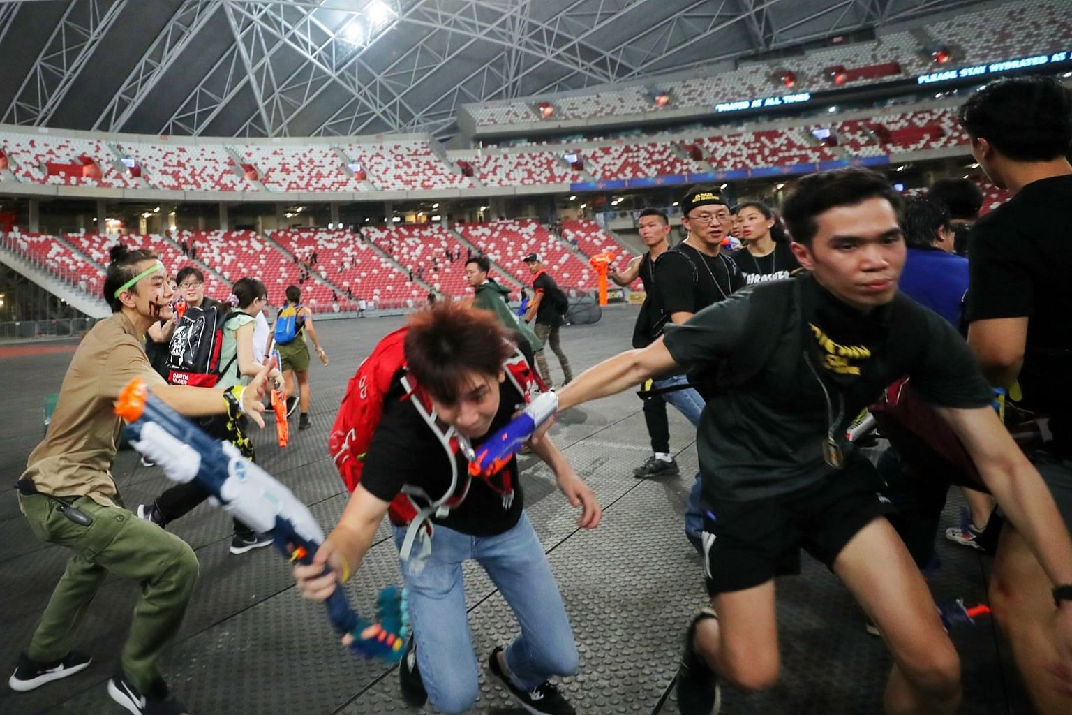 A zombie (in green headband) tries to catch a survivor at the live-action zombie survival game, Zedtown Asia: Battle For Singapore.