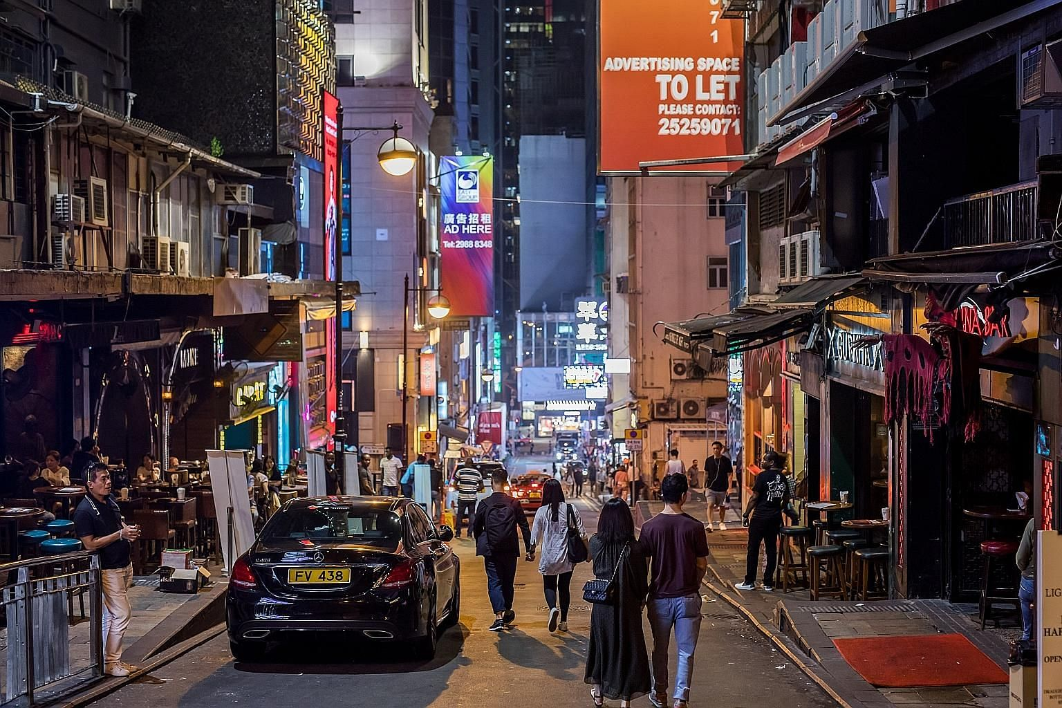 """Above: Financial Secretary Paul Chan said measures to support local small and medium-sized enterprises can only """"slightly reduce the pressure"""". Left: Hong Kong's nightlife hot spot Lan Kwai Fong on Sunday. Mr Chan described the plunge in tourist arri"""