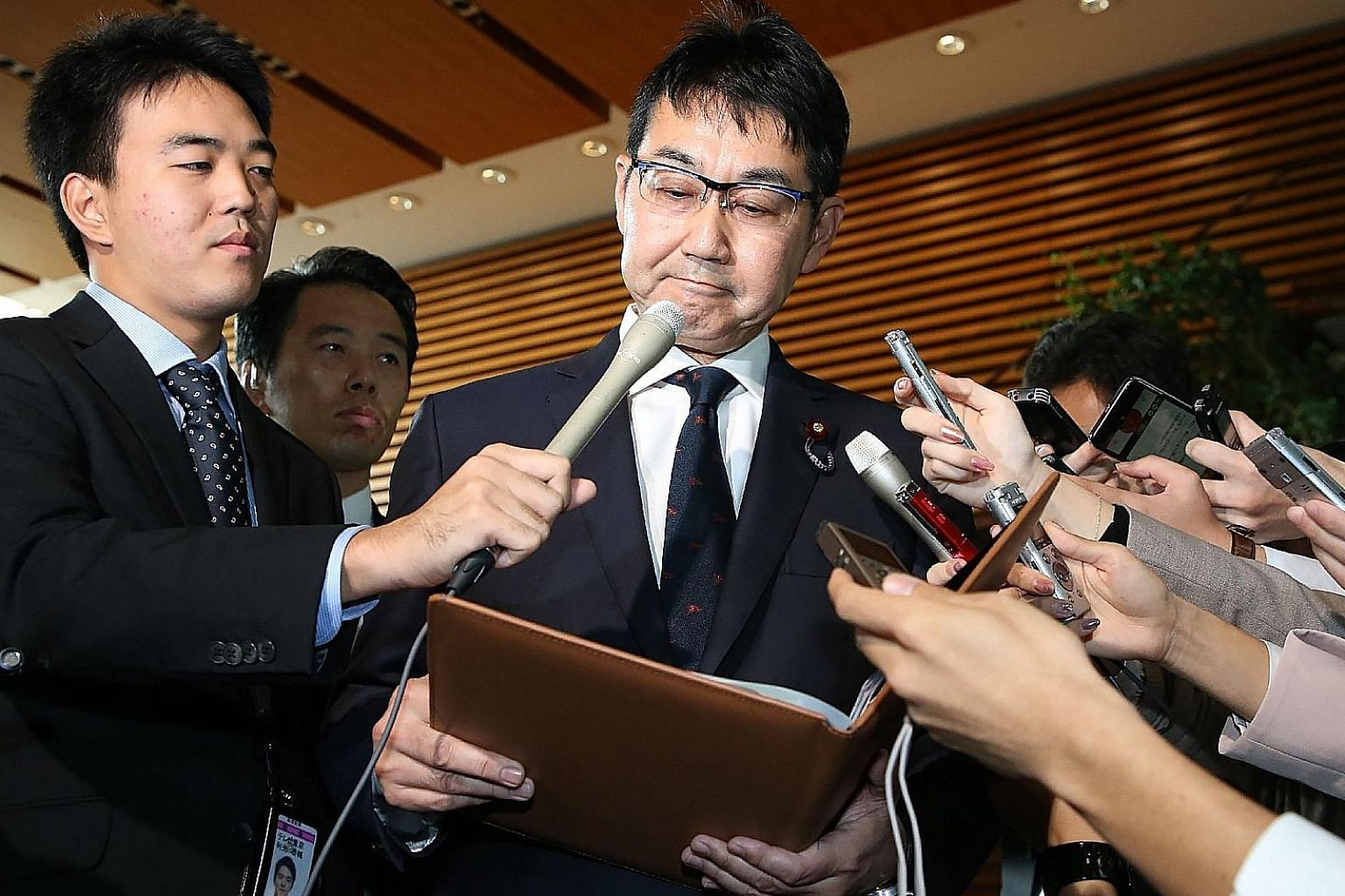 Japan's Justice Minister Katsuyuki Kawai speaking to journalists in Tokyo yesterday after submitting his resignation. He was alleged to have given potatoes, corn and mangoes to voters.