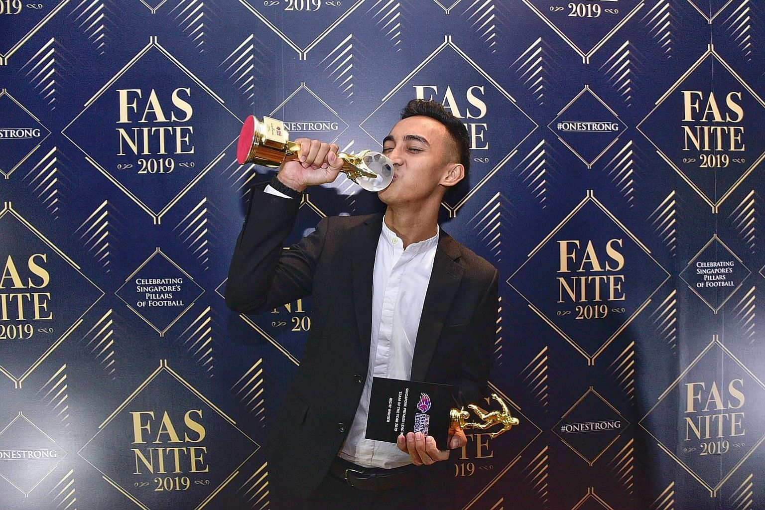 Hougang's Faris Ramli celebrating with his two trophies for winning the Player of the Year award and being named in the SPL Team of the Year at yesterday's FAS Nite 2019. ST PHOTOS: DESMOND WEE