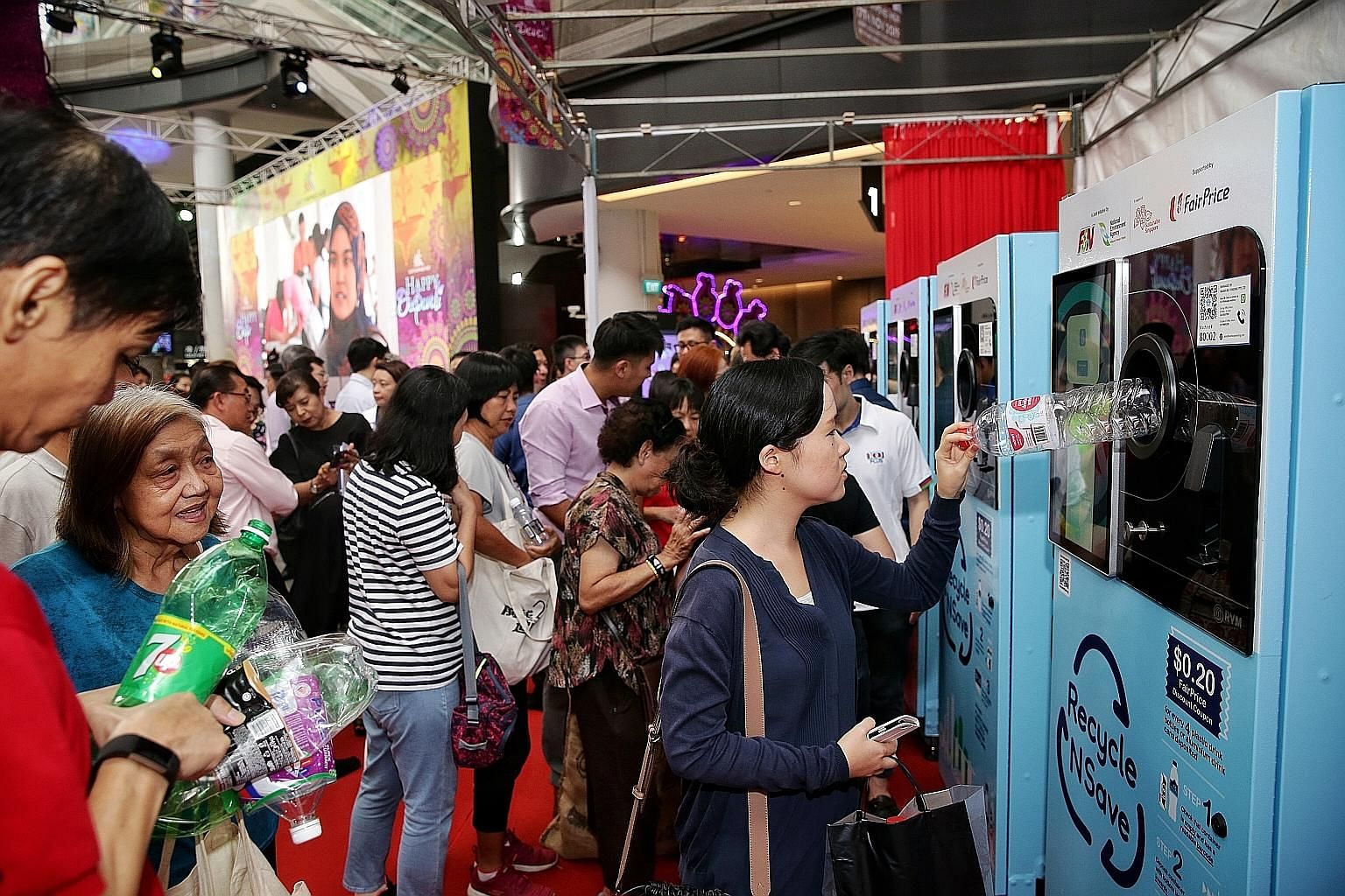 """Members of the public using the """"reverse"""" vending machines at the launch of the Recycle N Save initiative at Our Tampines Hub yesterday. For every four drink receptacles deposited, a discount voucher worth 20 cents that can be used at any FairPrice,"""