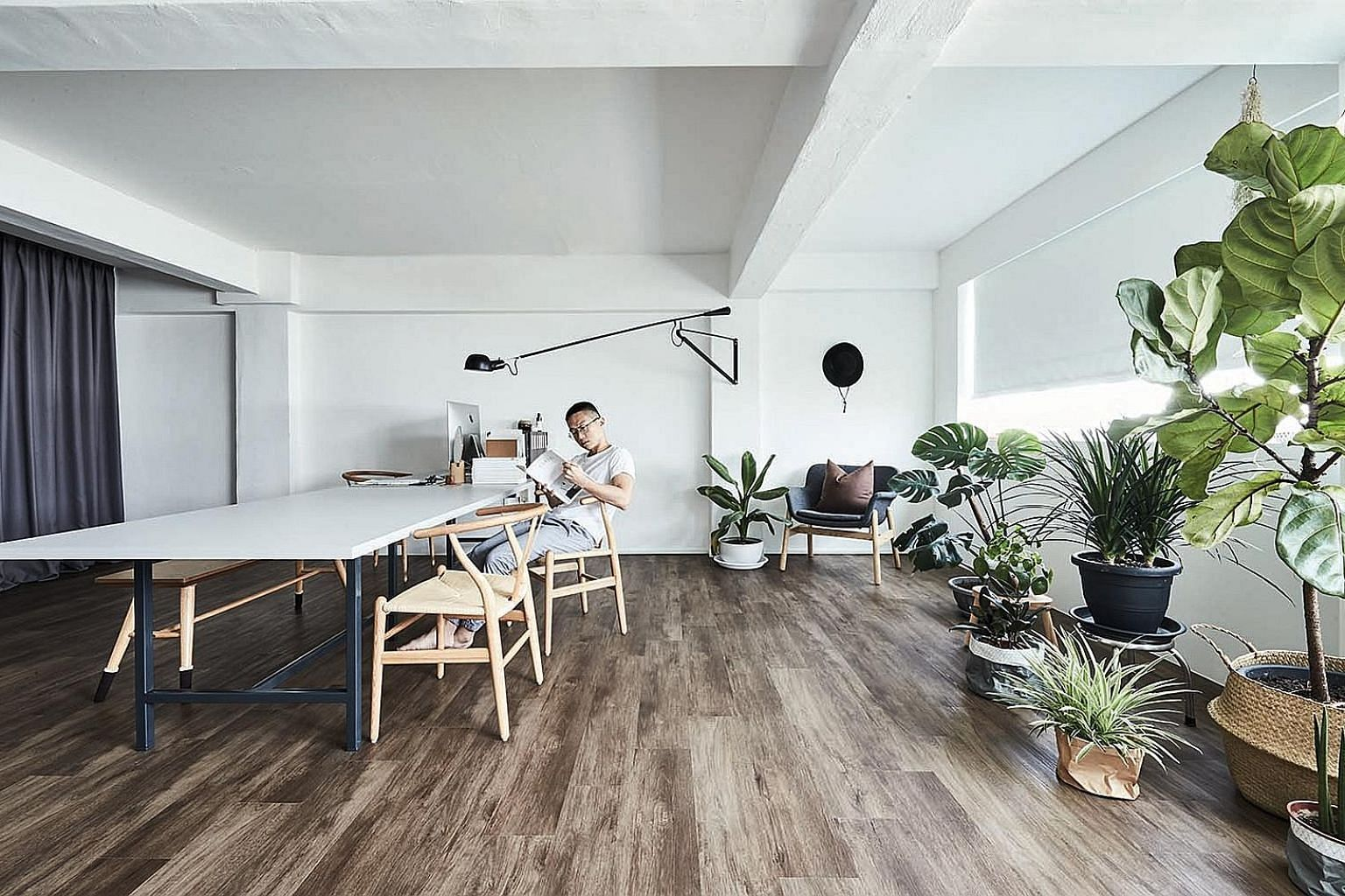 The Hans J. Wegner Wishbone Chairs are favoured by home owner Chia Ching Kai for their ergonomic design and comfort. A sense of fluidity and a fuss-free vibe permeate the minimalist apartment, from the sleeping area (above) to the kitchen (top). An a