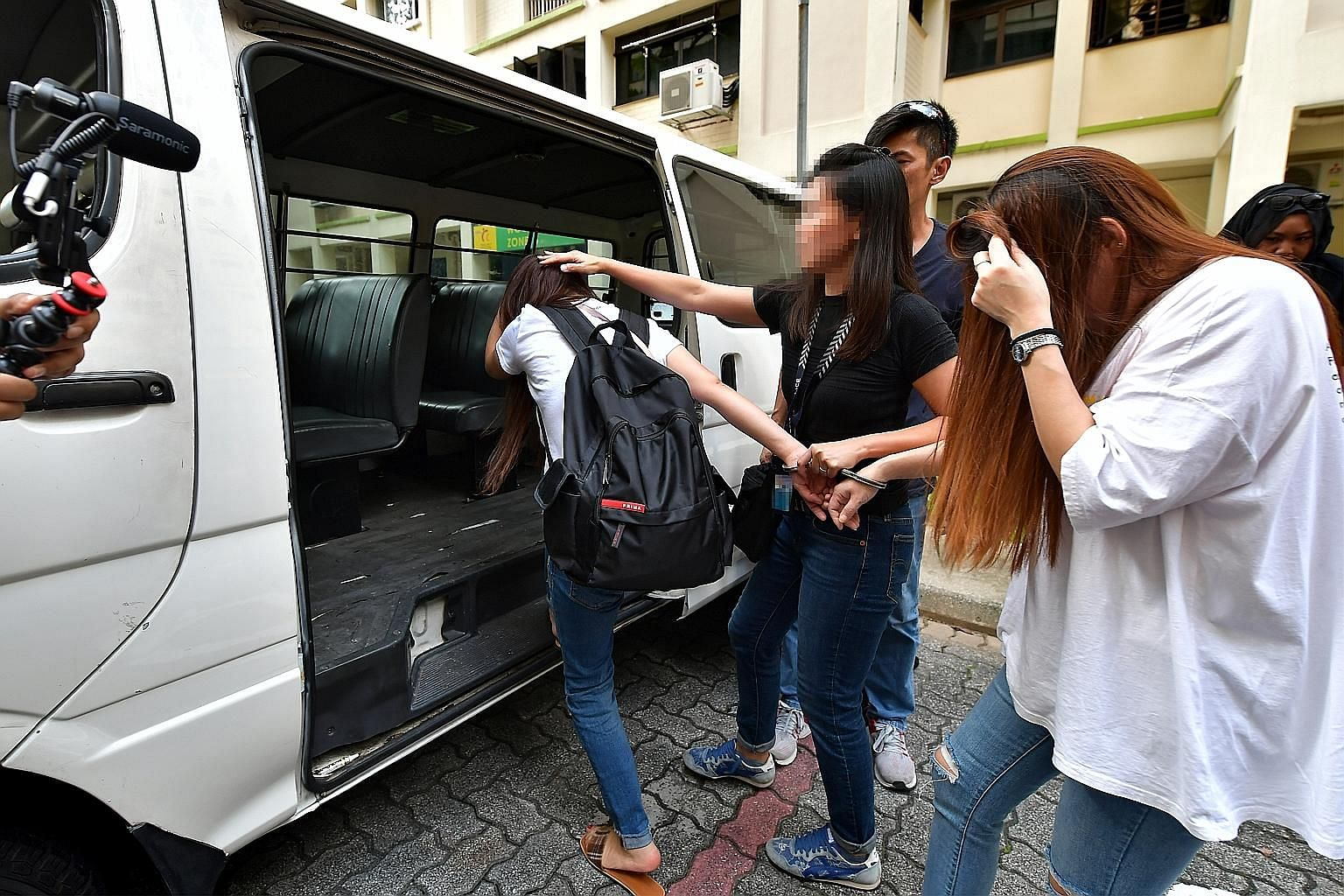 Two women being led away by the police on Oct 25 for suspected involvement in vice-related activities in a Housing Board flat in Woodlands. ST PHOTO: NG SOR LUAN