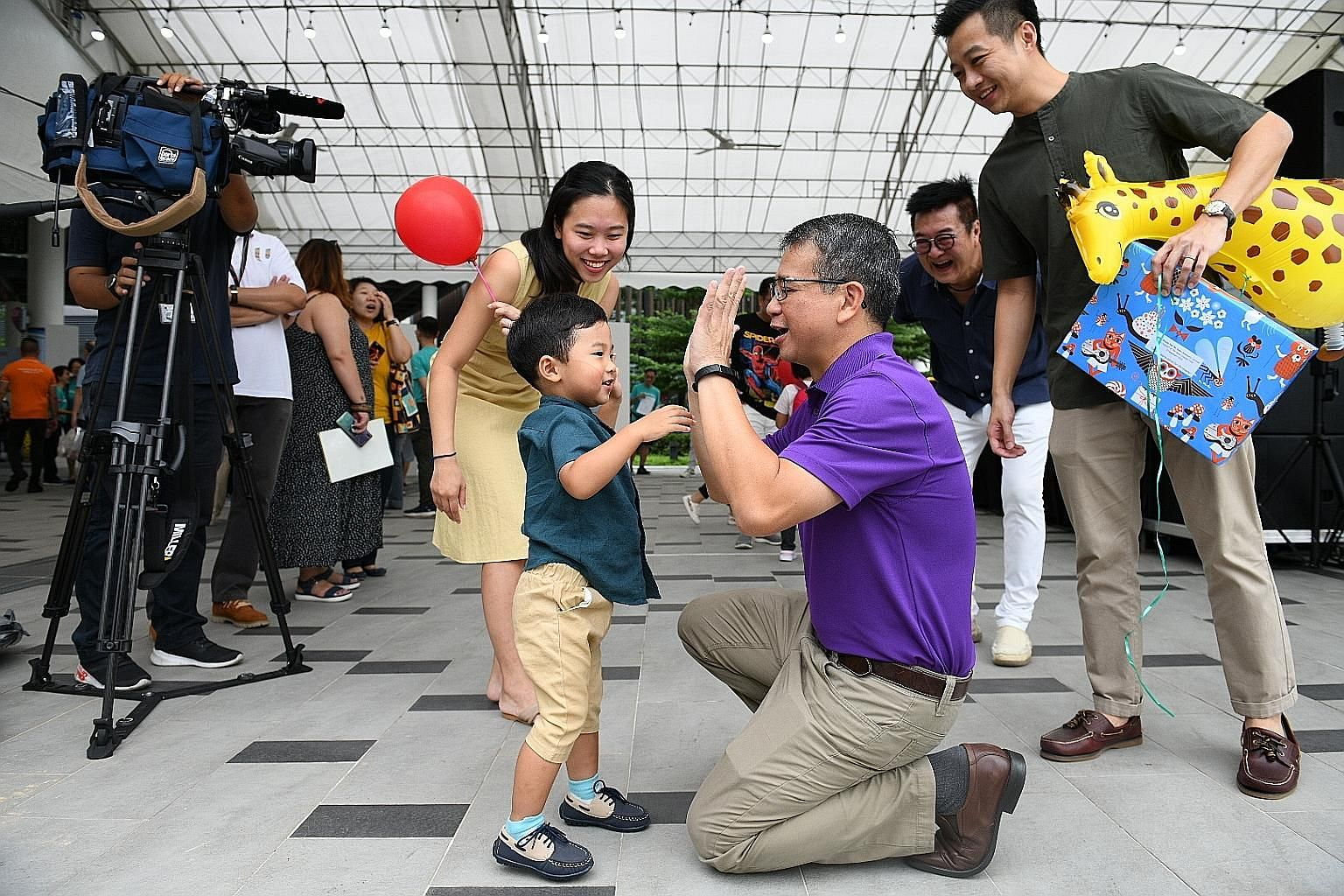 Public servant Geoffrey Toi and his wife, Straits Times correspondent Amelia Teng, watching as their three-year-old son Christopher interacted with Senior Minister of State for Health and Law Edwin Tong at the Punggol carnival organised by Mount Alve
