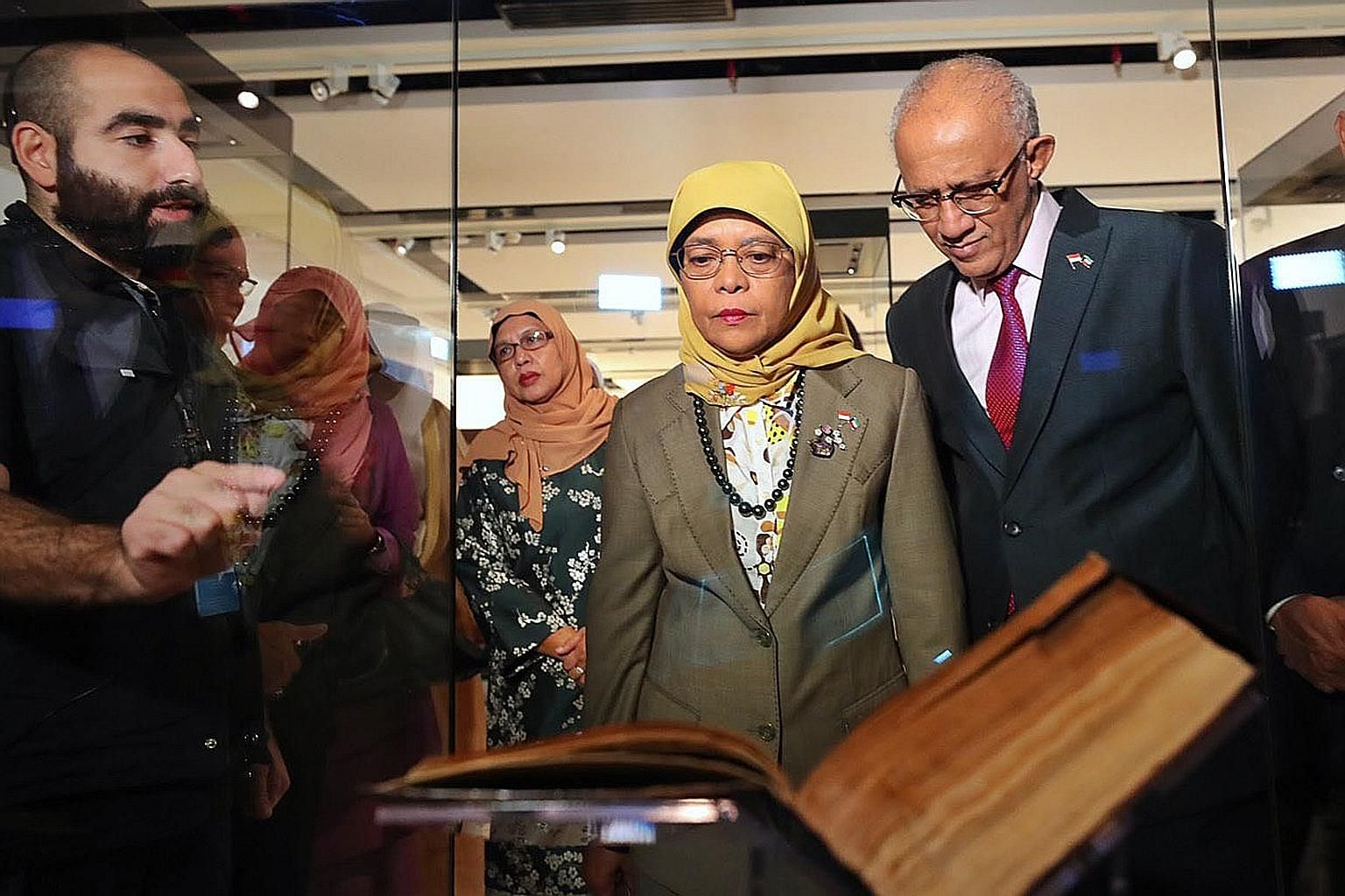 President Halimah Yacob and her husband Mohamed Abdullah Alhabshee looking at exhibits in the Sheikh Abdullah Al Salem Cultural Centre.