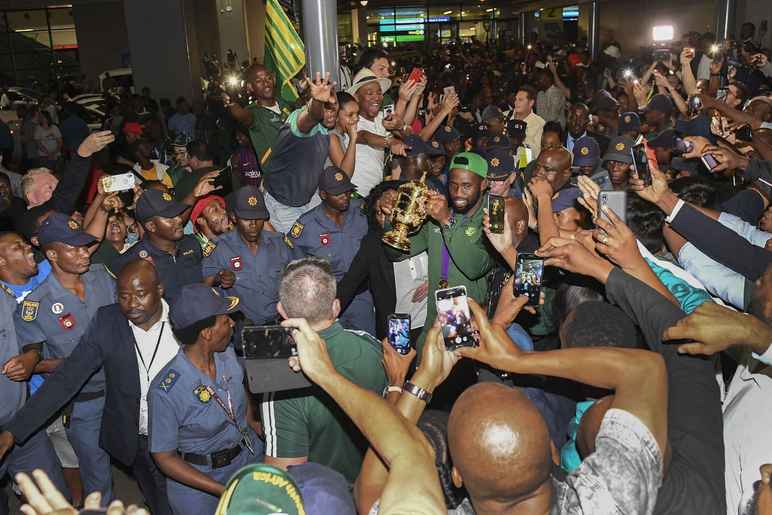 South Africa captain Siya Kolisi holding the Webb Ellis Trophy while walking through the throng of supporters who turned up at the airport to fete the return of the Springboks. PHOTO: EPA-EFE