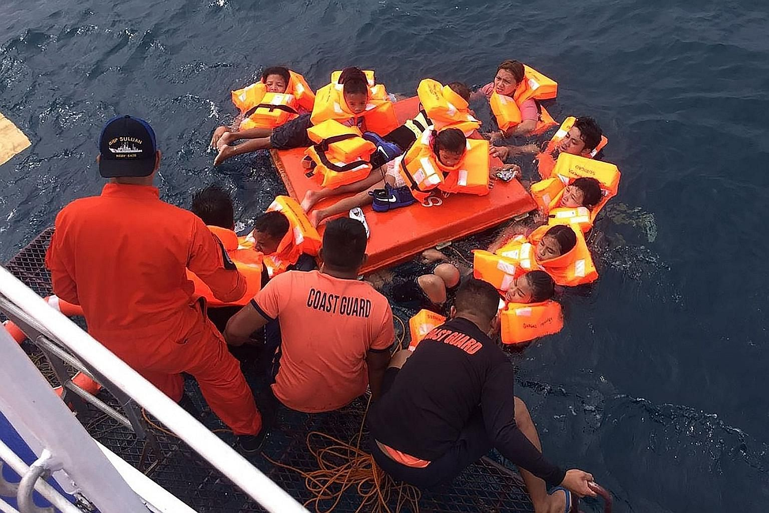 Some of the 59 people plucked out of the water by the Philippine Coast Guard after a ferry capsized in rough seas near the island of Cebu yesterday, in this handout photo from the coast guard. Another three who had been on board managed to swim to sh