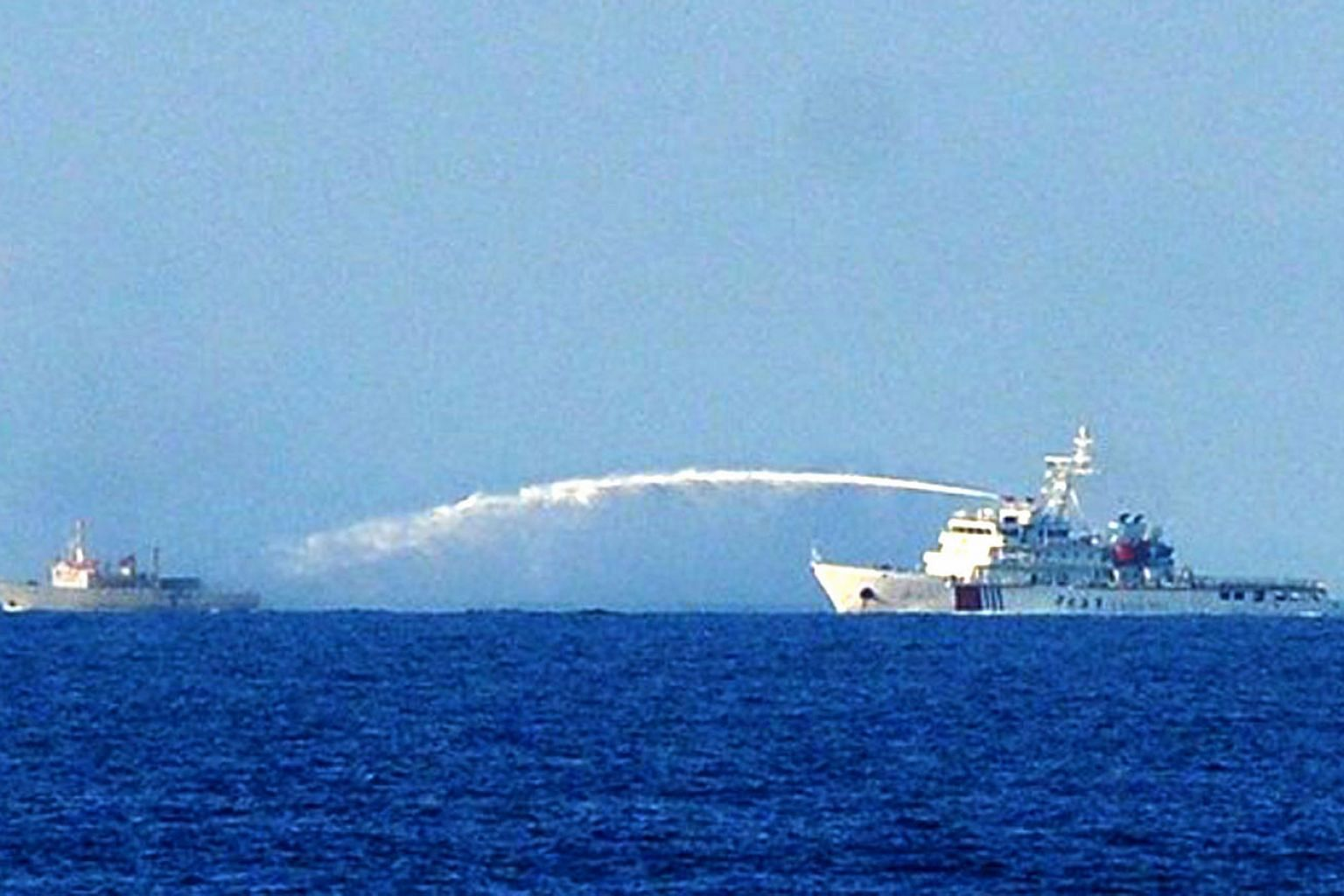 A Chinese coast guard ship (right) using a water cannon on June 2, 2014, on a Vietnamese fisheries surveillance boat near a Chinese oil rig off Vietnam's central coast. As Asean chairman, Vietnam will bear in mind the need to build Asean consensus on
