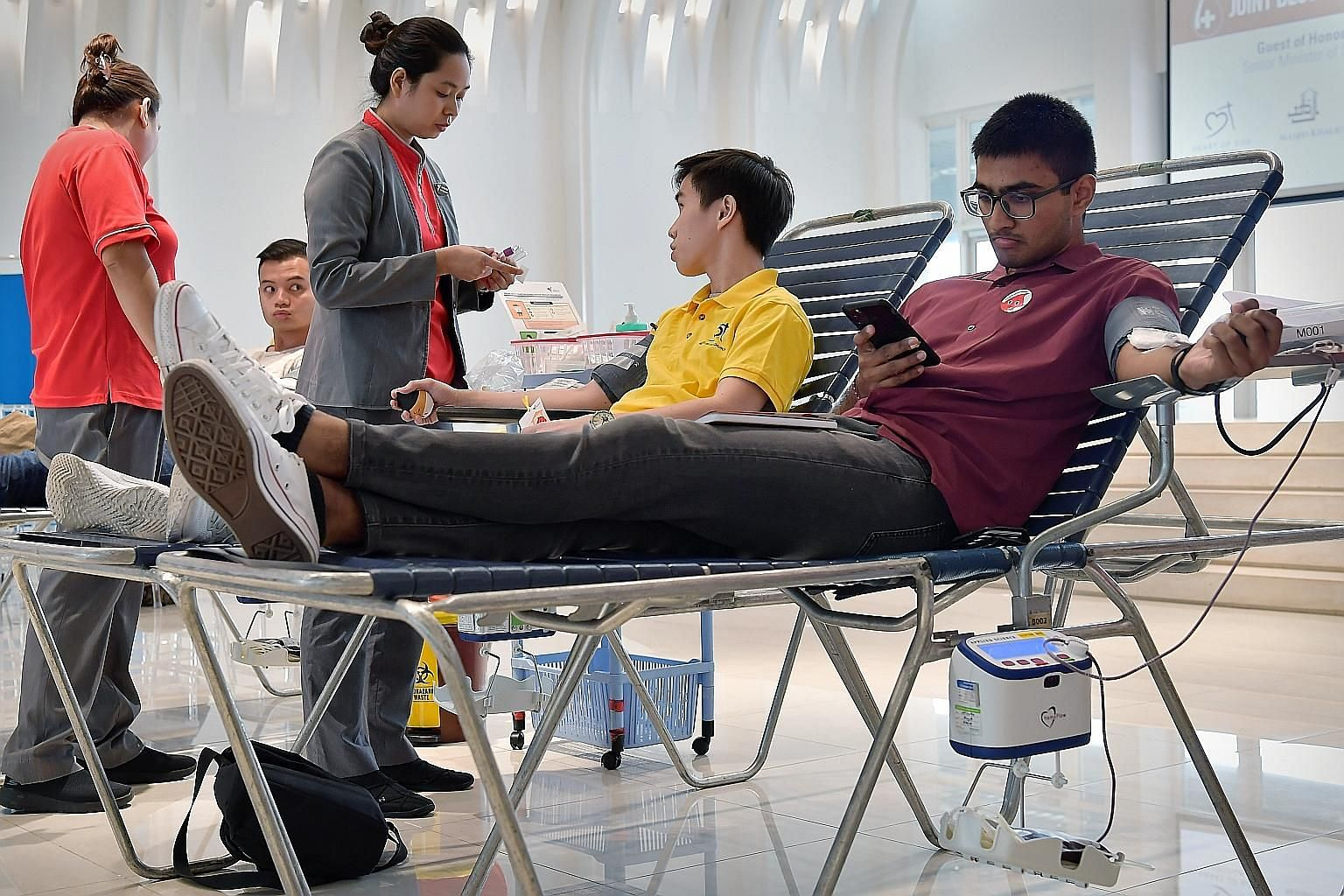 Mr Vamsi Krishna, 21, and student Bowen Ong (in yellow), 18, were among about 200 people who donated blood at the event held jointly by Heart of God Church, Khalid Mosque, Geylang United Temple and Nanyang Leow-Sih Association yesterday.