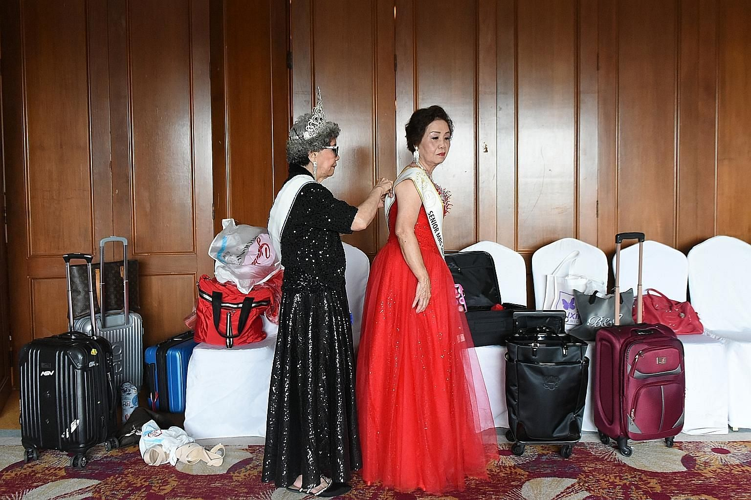 Last year's TKS Mrs Senior Singapore champion, Madam Teh Siew Peng (left), 77, helping Madam Kan Yuet Chee, 79, with her evening dress for a pre-pageant dinner at Orchid Country Club last Thursday, the night before the finale. Madam Kan dancing with