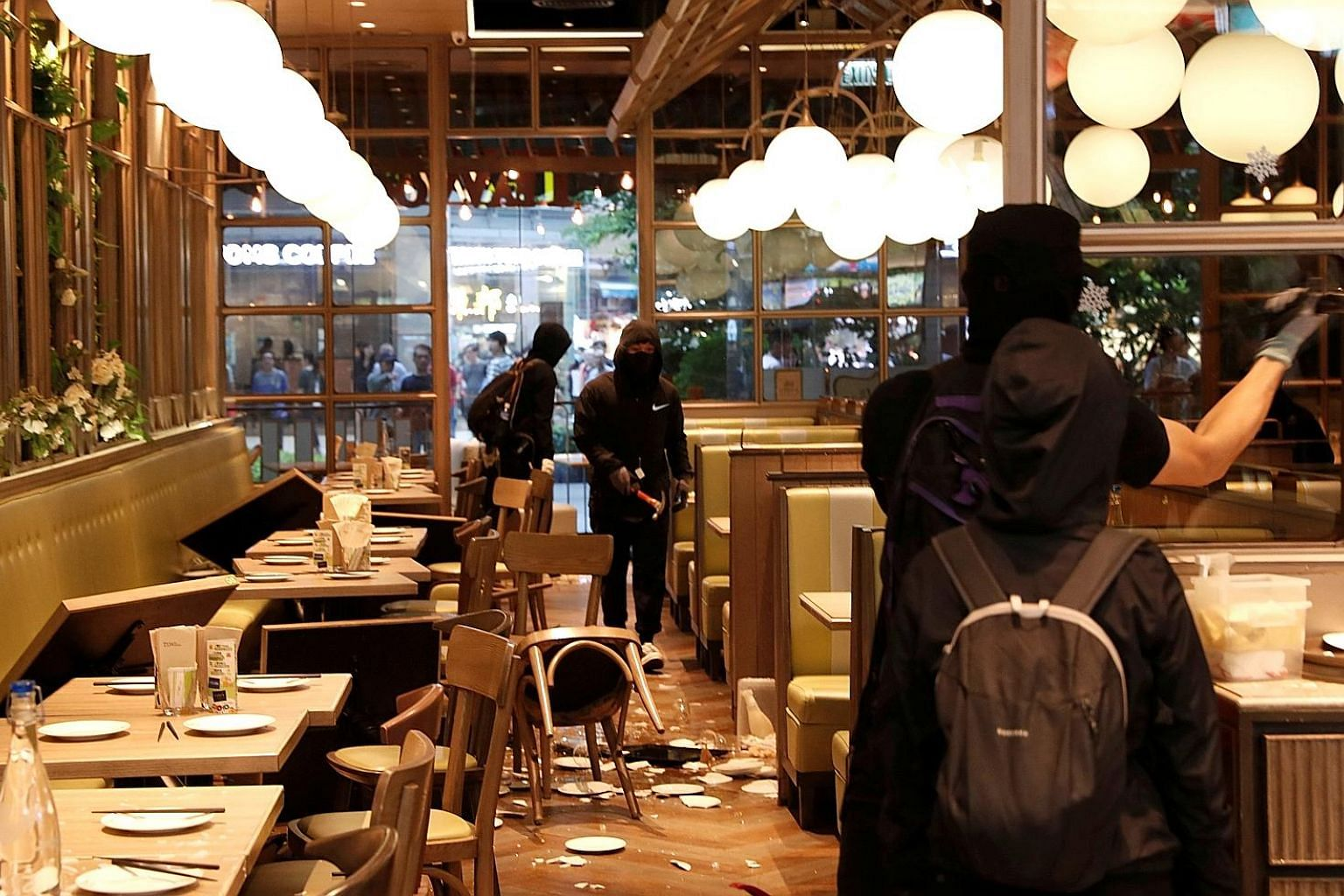Protesters vandalising a restaurant during an anti-government demonstration at a shopping mall in Tsuen Wan, Hong Kong, yesterday. Some protesters had trashed several shops in Sha Tin linked to the Maxim Catering Group, including a Starbucks and a Ma
