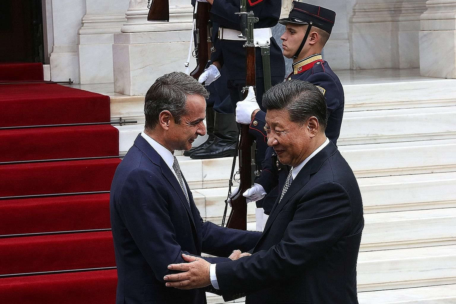 """Greek Prime Minister Kyriakos Mitsotakis welcoming Chinese President Xi Jinping to Athens yesterday. Mr Xi said China and Greece """"are natural partners"""" in the creation of China's Belt and Road Initiative."""
