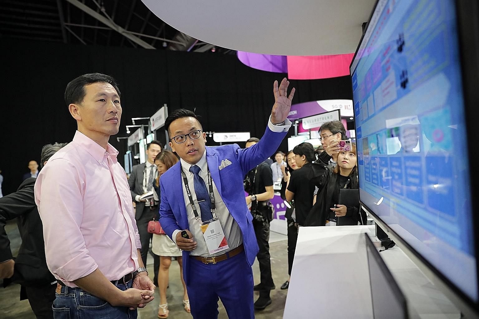 Education Minister Ong Ye Kung visiting ST Engineering's booth at the Singapore FinTech Festival yesterday. With him was Mr Tan Boon Leong, a senior system consultant (data analytics) from ST Engineering.