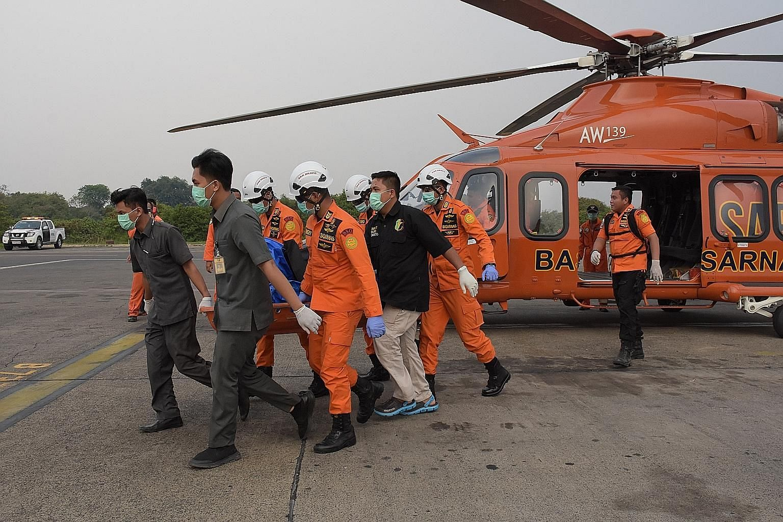 Rescue workers with the body of one of the three divers who went missing last Sunday at an airport in Jakarta yesterday. Fishermen had earlier found the body in waters near Lampung province.