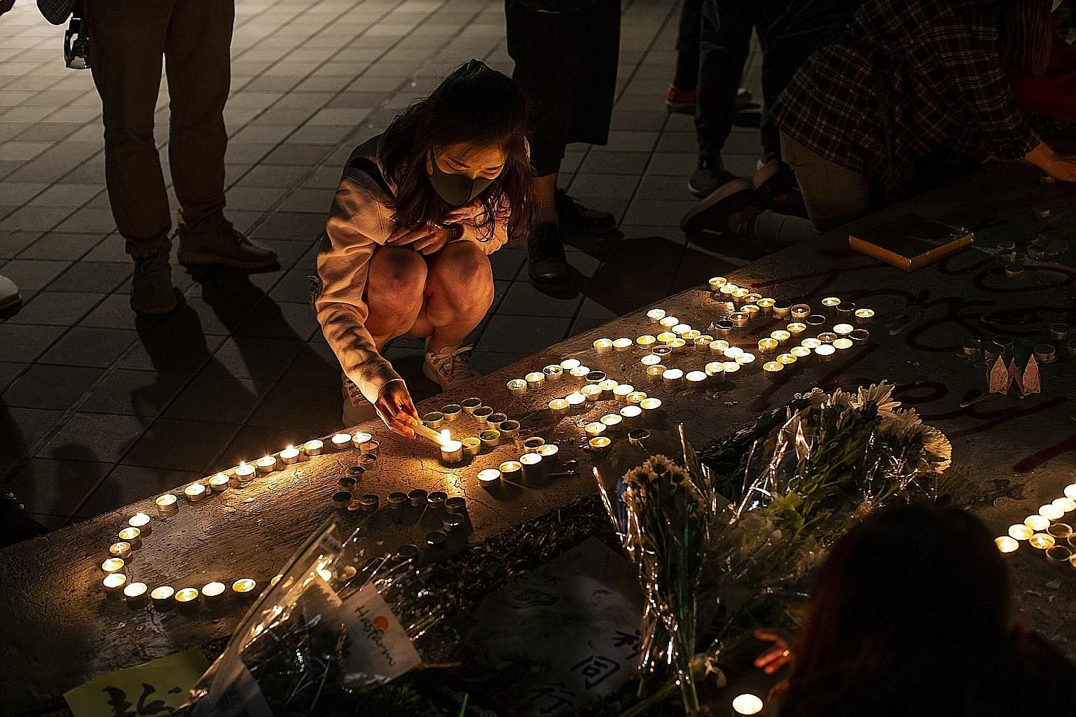 People lighting candles last Saturday to commemorate university student Chow Tsz Lok, 22, who died on Nov 8 after falling one floor from a parking lot during police action to disperse protesters. PHOTO: BLOOMBERG