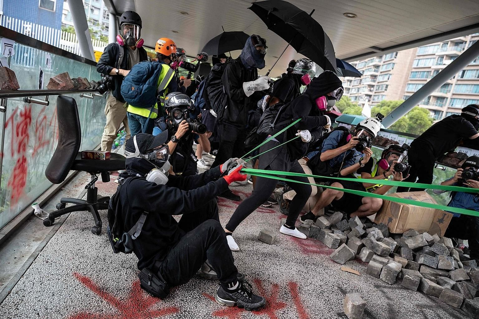 A protester (above) using a catapult against the police at Hong Kong's City University yesterday. The biggest stand-offs took place at the Chinese University of Hong Kong, where pitched battles continued throughout the day. Protests elsewhere disrupt