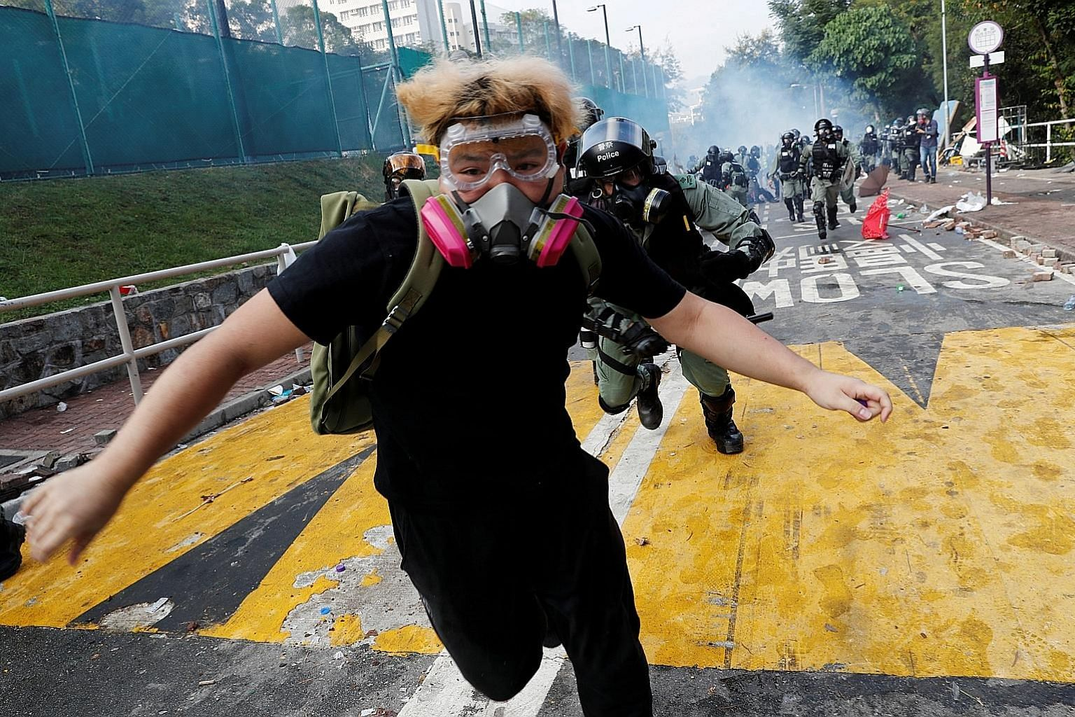 A university student running from riot police at the Chinese University of Hong Kong (CUHK) yesterday. Universities have emerged as a new battleground with sustained clashes at major campuses for the first time. Police fired tear gas at City Universi