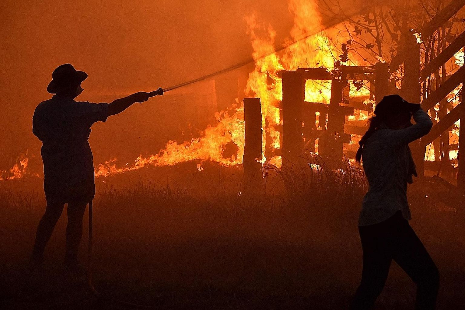 """Residents defending a property from a bush fire at Hillsville near Taree, 350km north of Sydney, yesterday. A state of emergency was declared on Monday, and residents in the Sydney area were warned of """"catastrophic"""" fire danger as Australia prepared"""