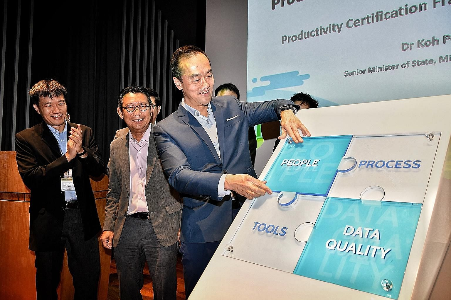 Senior Minister of State for Trade and Industry Koh Poh Koon fixing a piece of a puzzle comprising four areas that firms will be evaluated on, at the launch of the certification framework yesterday. With him at the Trade Association Hub in Jurong Eas
