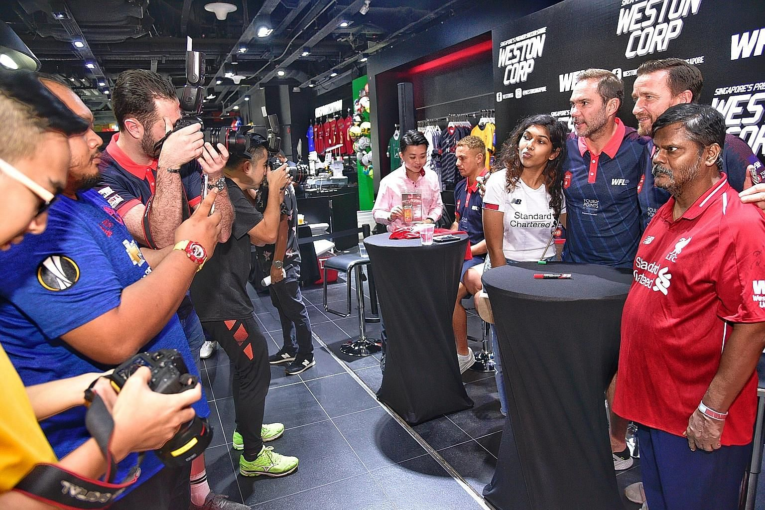 Marketing executive Rajeswari Anbalagan, 23, and her father, retiree K.R. Anbalagan, 57, flanking former Liverpool players Jason McAteer and Vladimir Smicer during the meet and greet with fans at sportswear store Weston in Kallang Wave Mall, ahead of