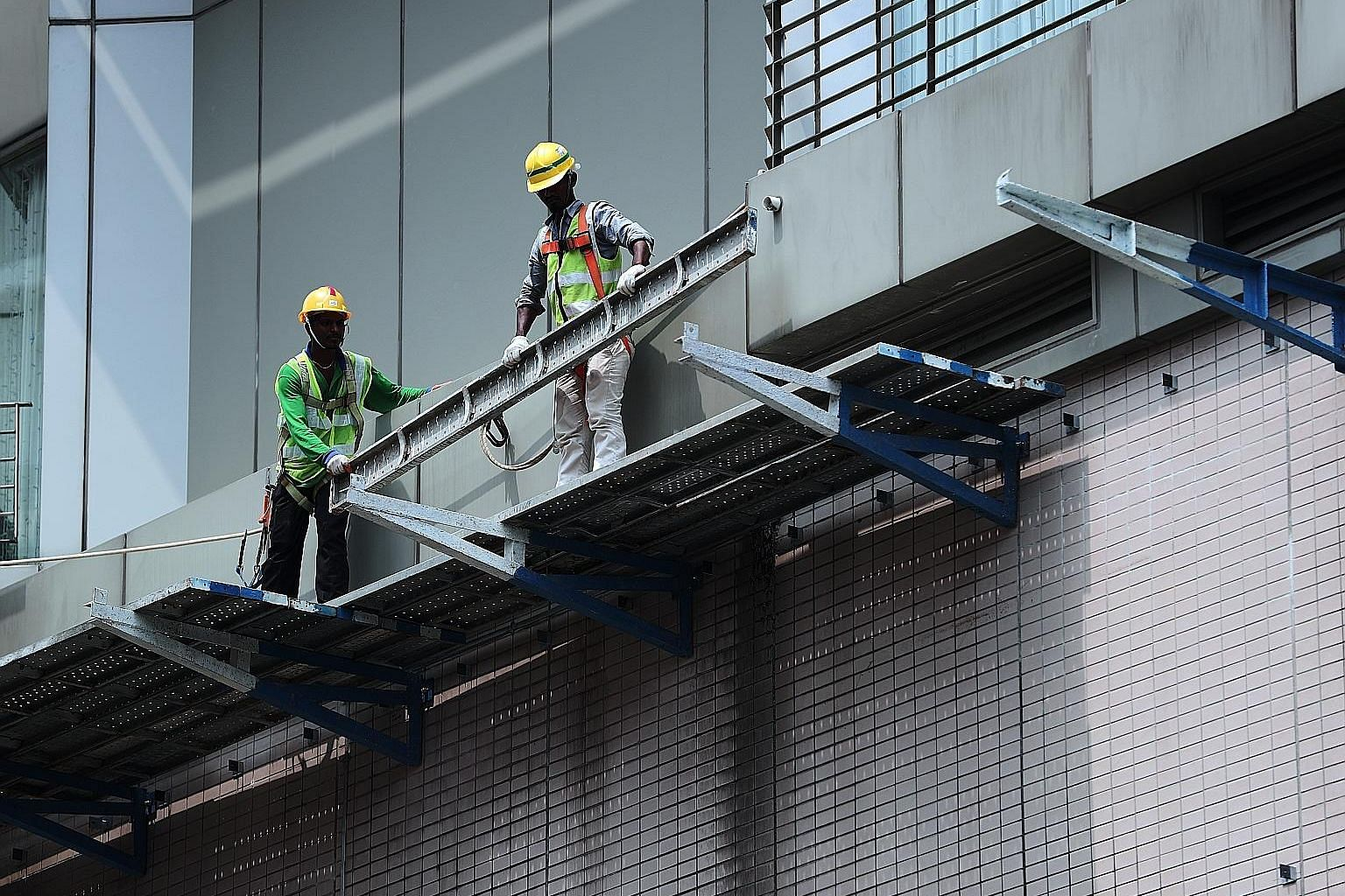 Workers using safety harnesses while working at a height. Last year, eight workers died as a result of a fall from height, down from 24 in 2009. ST PHOTO: KELVIN CHNG
