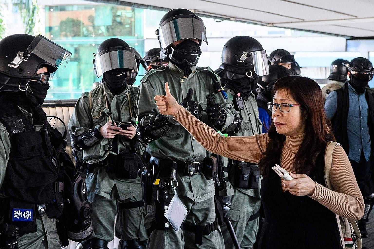 A woman exchanging a thumbs up with a police officer while walking past him on a footbridge in Hong Kong on Monday. A survey in mid-October by The Chinese University of Hong Kong showed some 41.4 per cent of respondents thought the use of radical tac