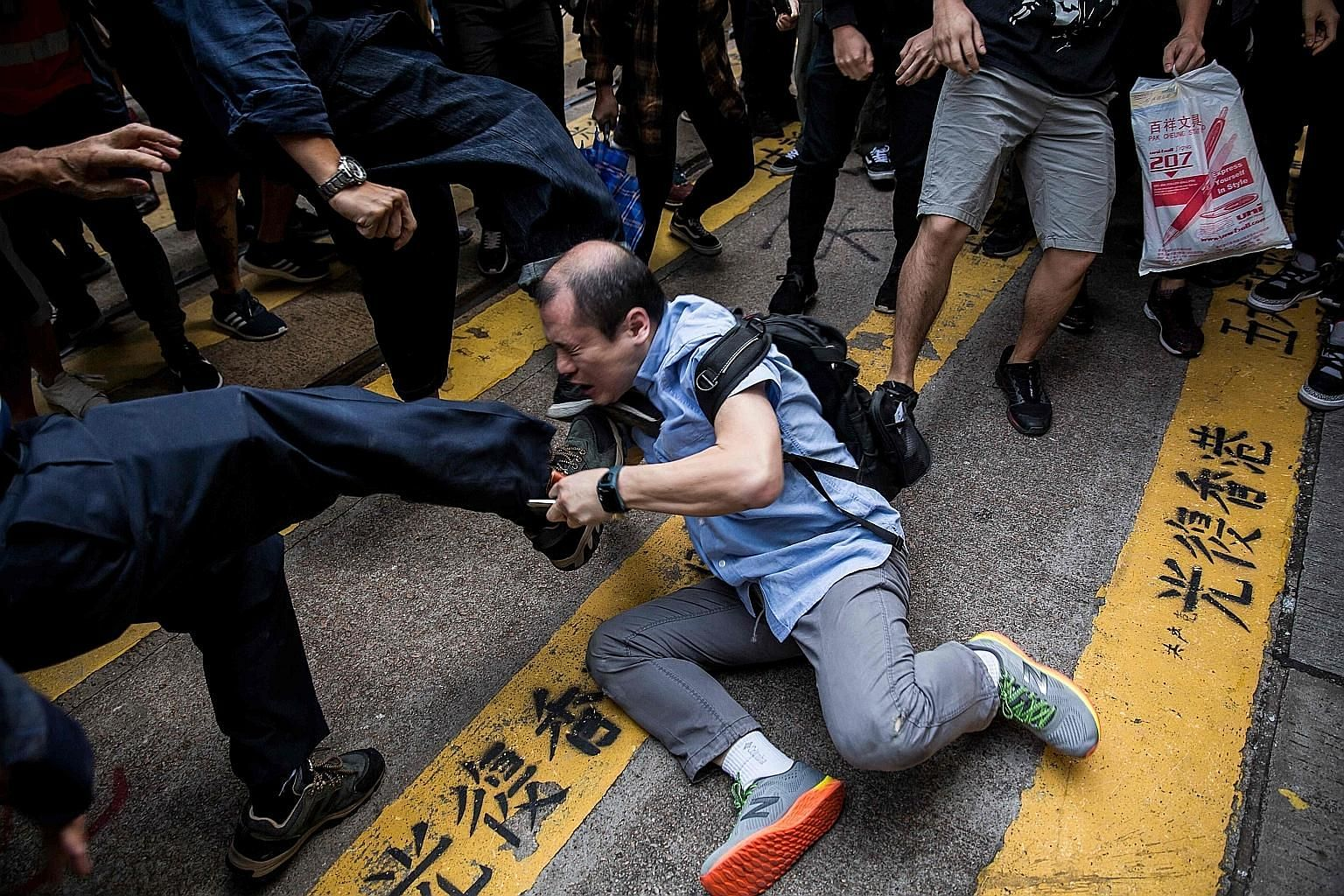 A man being beaten up after getting into an argument during a demonstration of office workers and protesters in Central, in Hong Kong, yesterday. The city's government confirmed yesterday that the police force would get reinforcements from 100 member