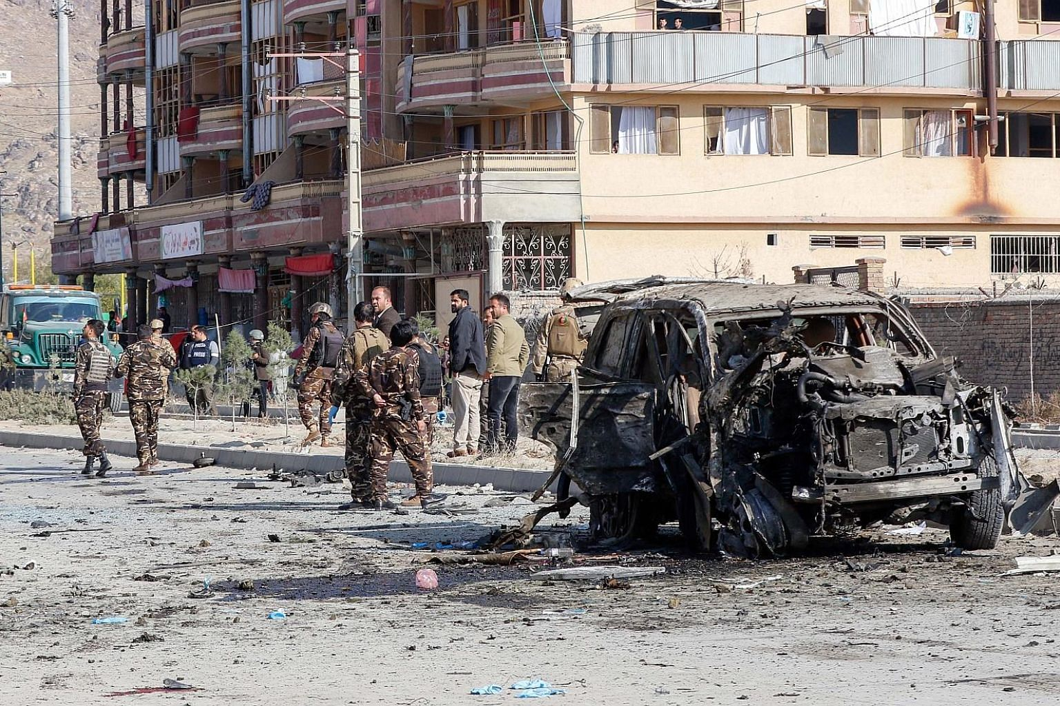 Afghan security forces inspecting the site of a car bomb attack, which targeted an armoured vehicle that belonged to GardaWorld - a Canadian security company that saw four of its staff wounded in the attack - in Kabul on Wednesday. PHOTO: EPA-EFE