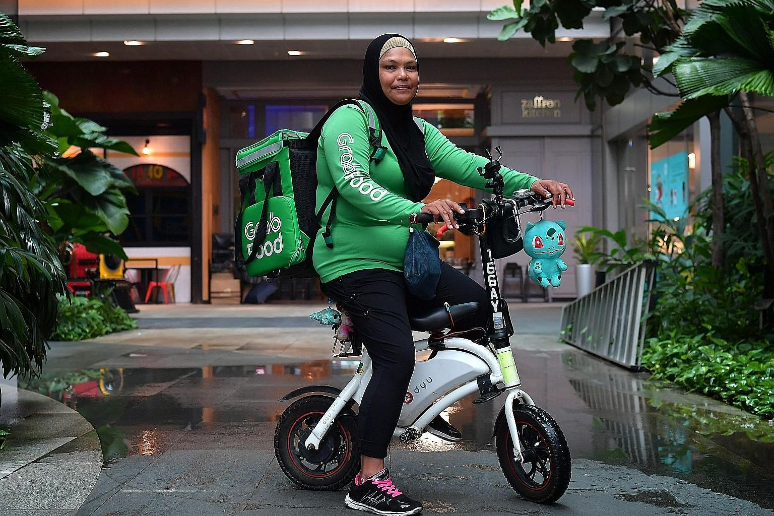 Being a GrabFood delivery rider lets Madam Afidah Amat structure work around ferrying her children to and from school.