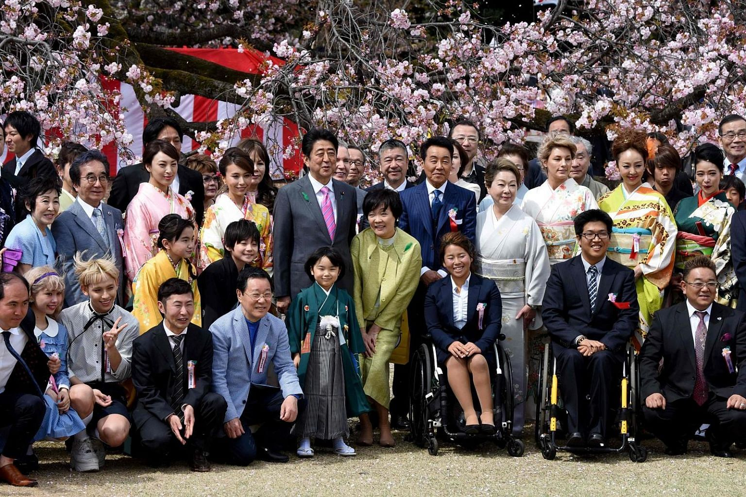 Japanese Prime Minister Shinzo Abe and his wife Akie (centre) posing with entertainers and athletes during the cherry blossom viewing party in Tokyo. The government said it would scrap next year's party after Mr Abe came under fire amid claims he inv