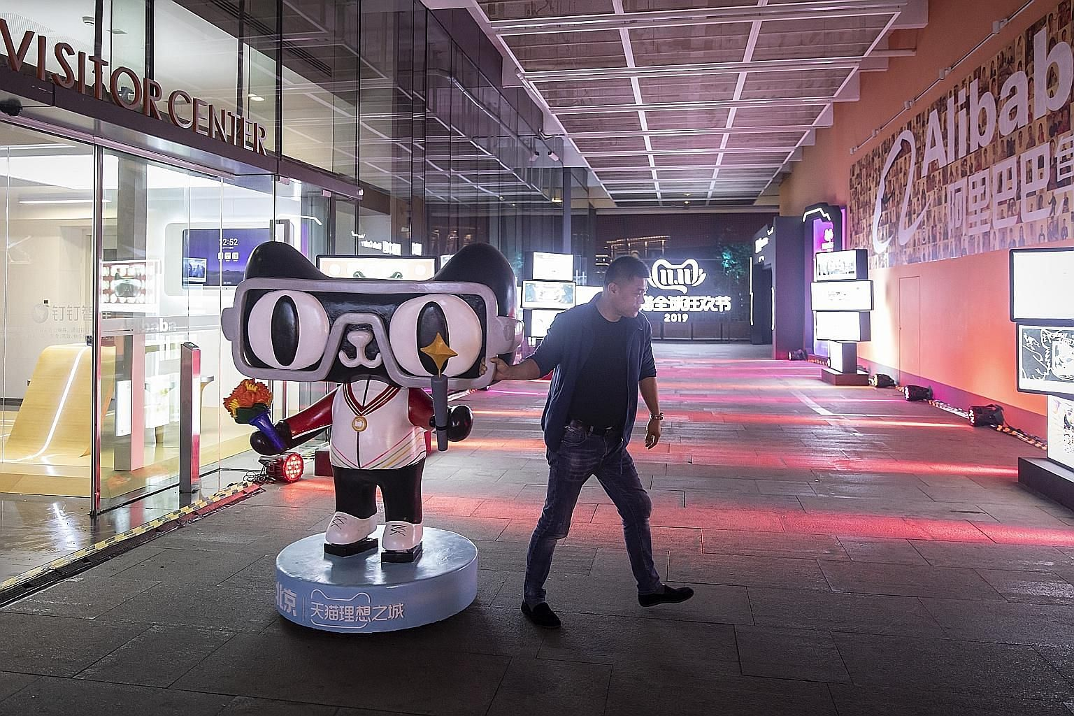 An employee moving a Tmall.com mascot at Alibaba's headquarters in Hangzhou. Alibaba's planned offering size for its initial public offering in Hong Kong has not changed as a result of the protests in the city, Mr Michael Yao, the company's head of c